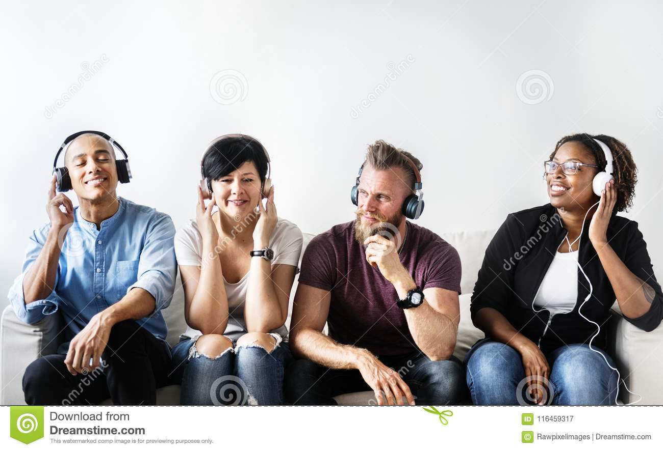 Diverse people sitting on the couch wearing headphones