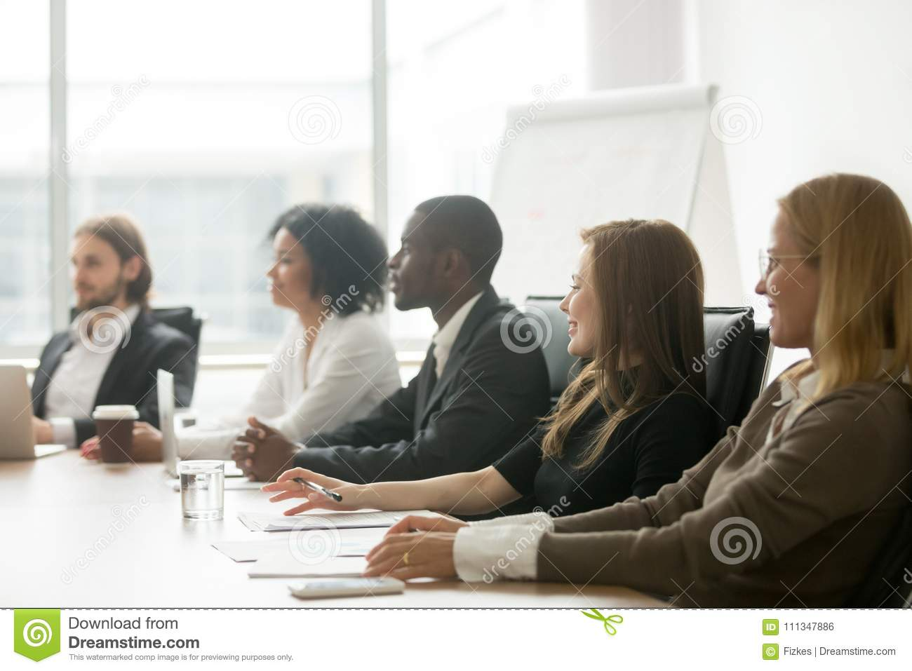 Diverse smiling businesspeople sitting at conference table at gr
