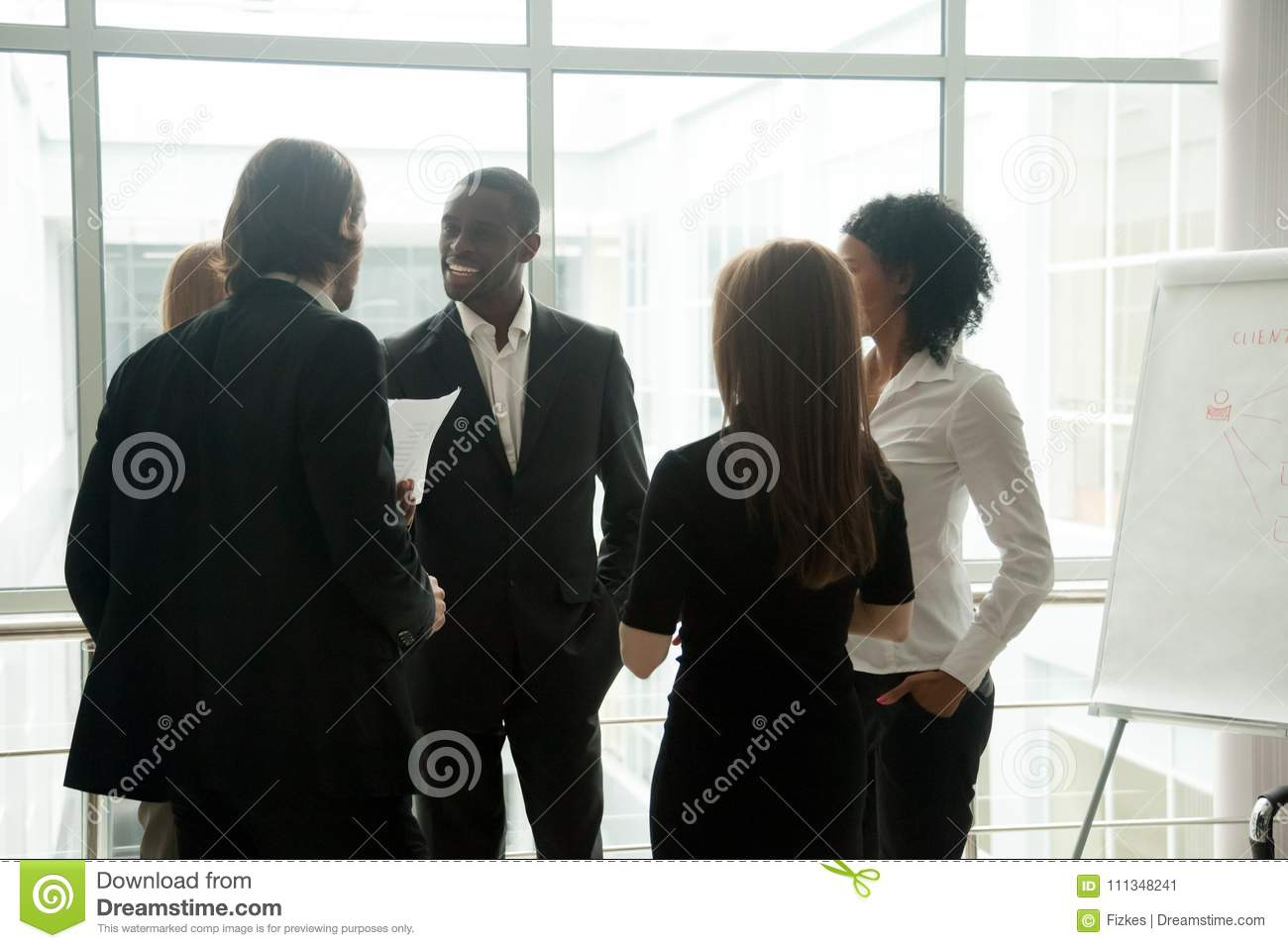Diverse smiling business people having conversation standing tog