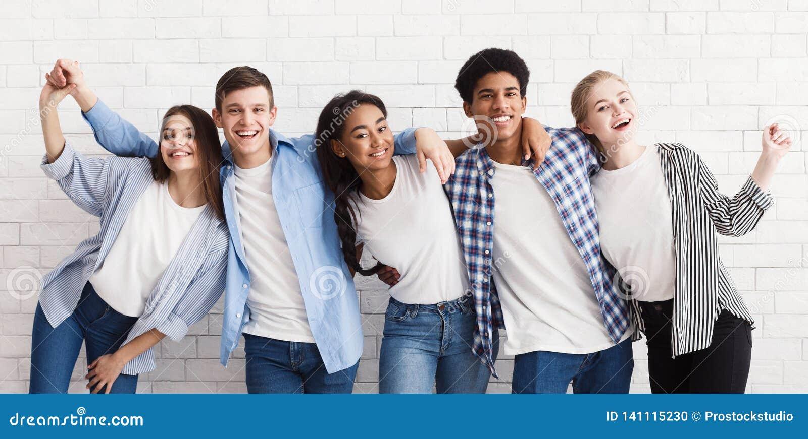 Diverse tieners die en pret over witte muur omhelzen hebben