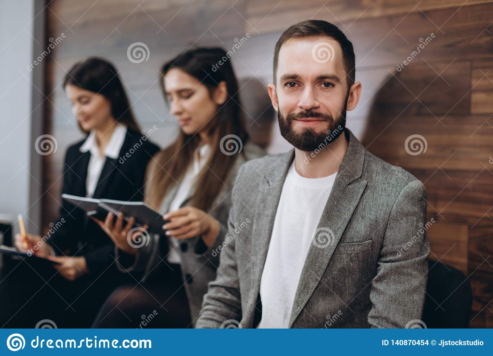 Diverse young businesspeople students friends sitting together in chairs in queue using mobile phones wait job interview or