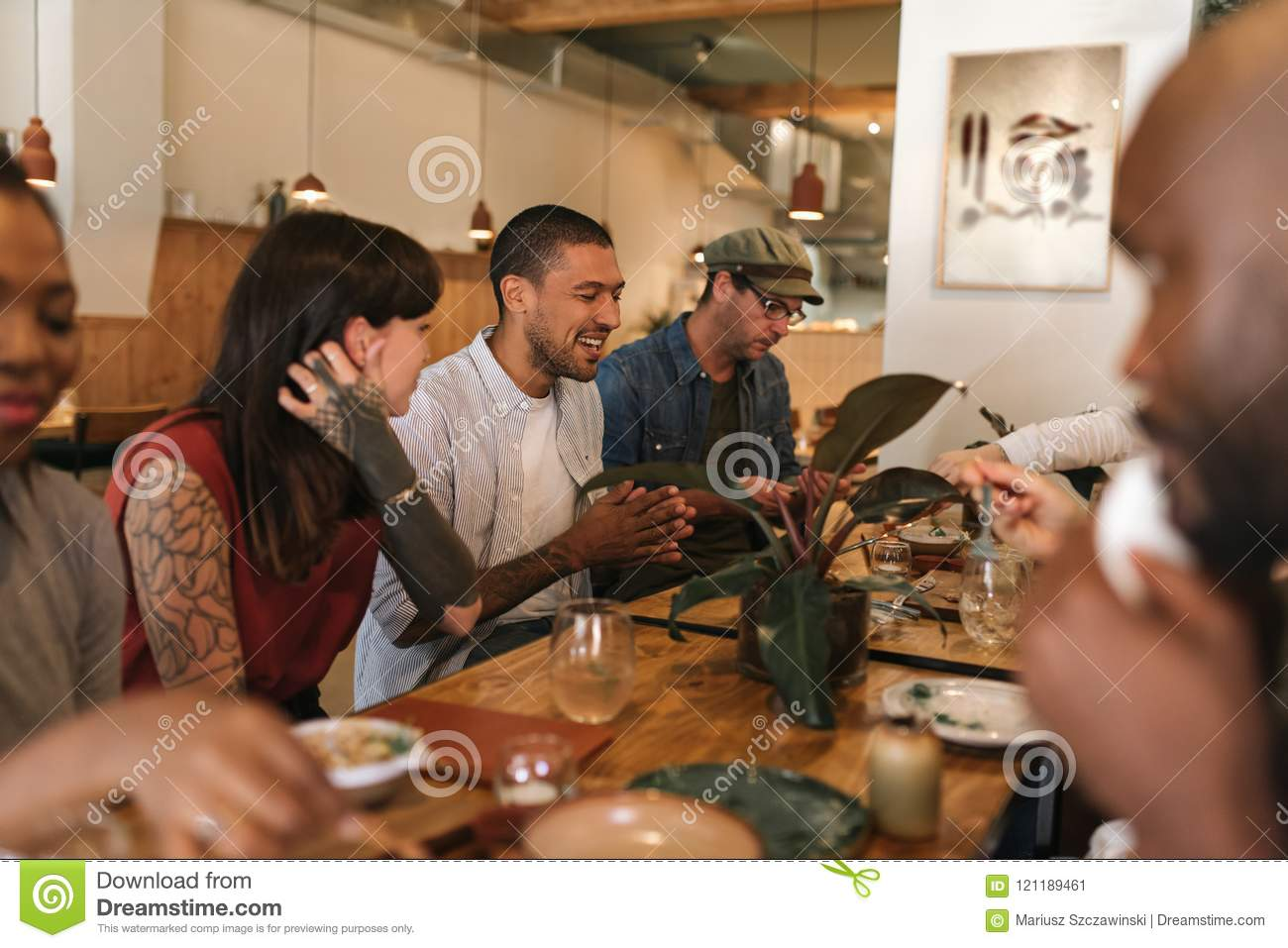 Diverse young friends having fun together over a bistro dinner