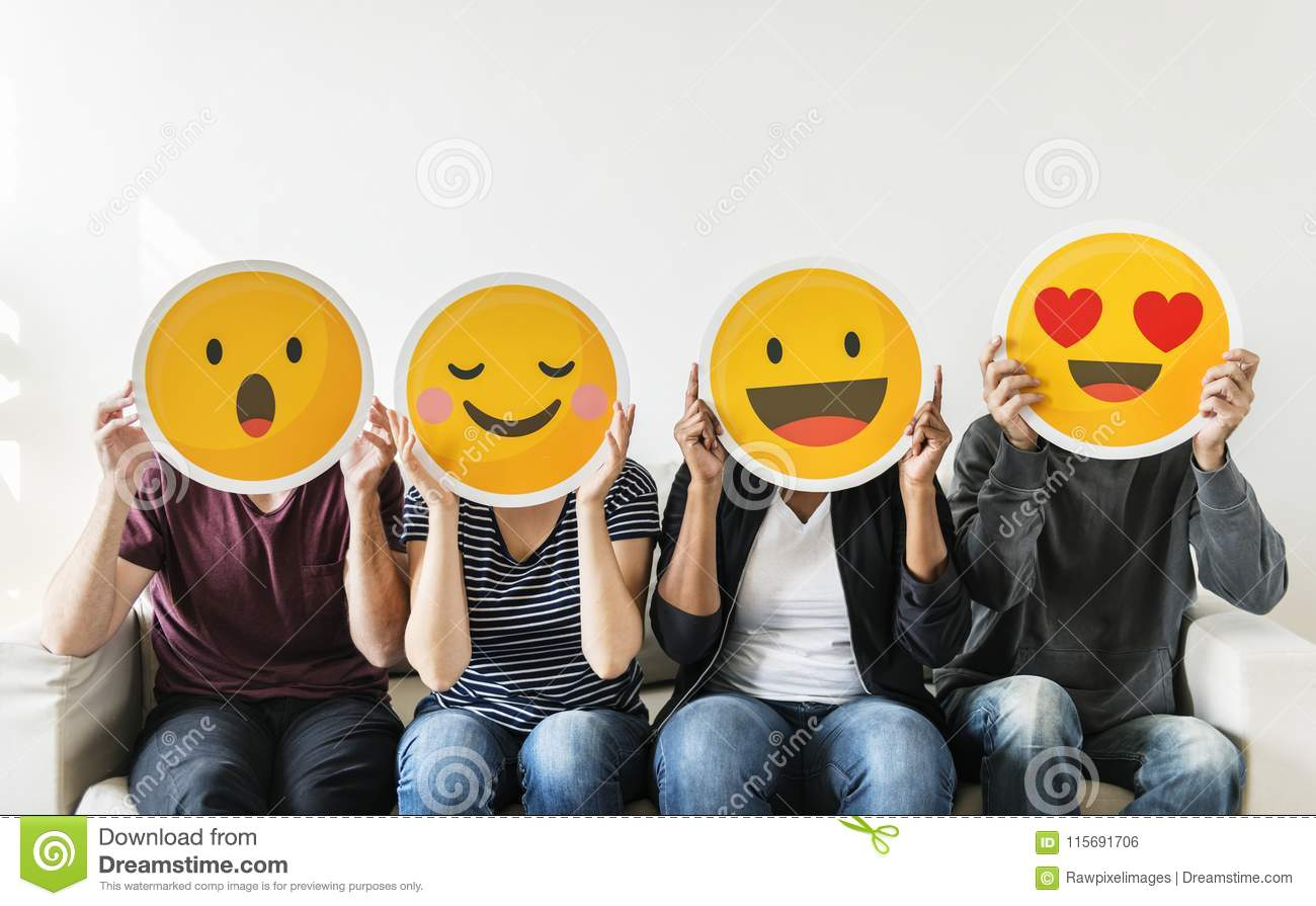 Diverse young people holding emoticon