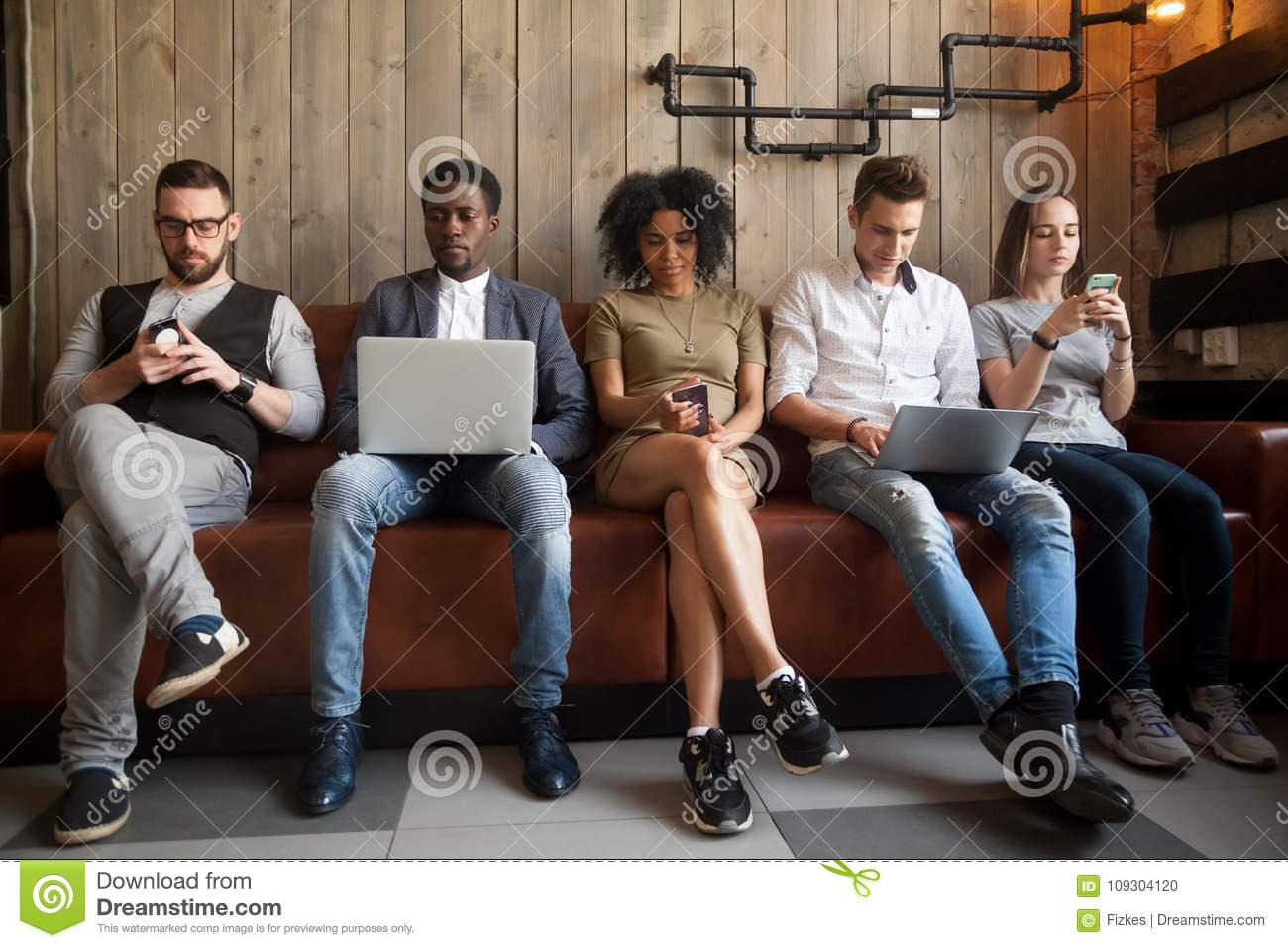 Diverse young people sitting in row obsessed with devices online