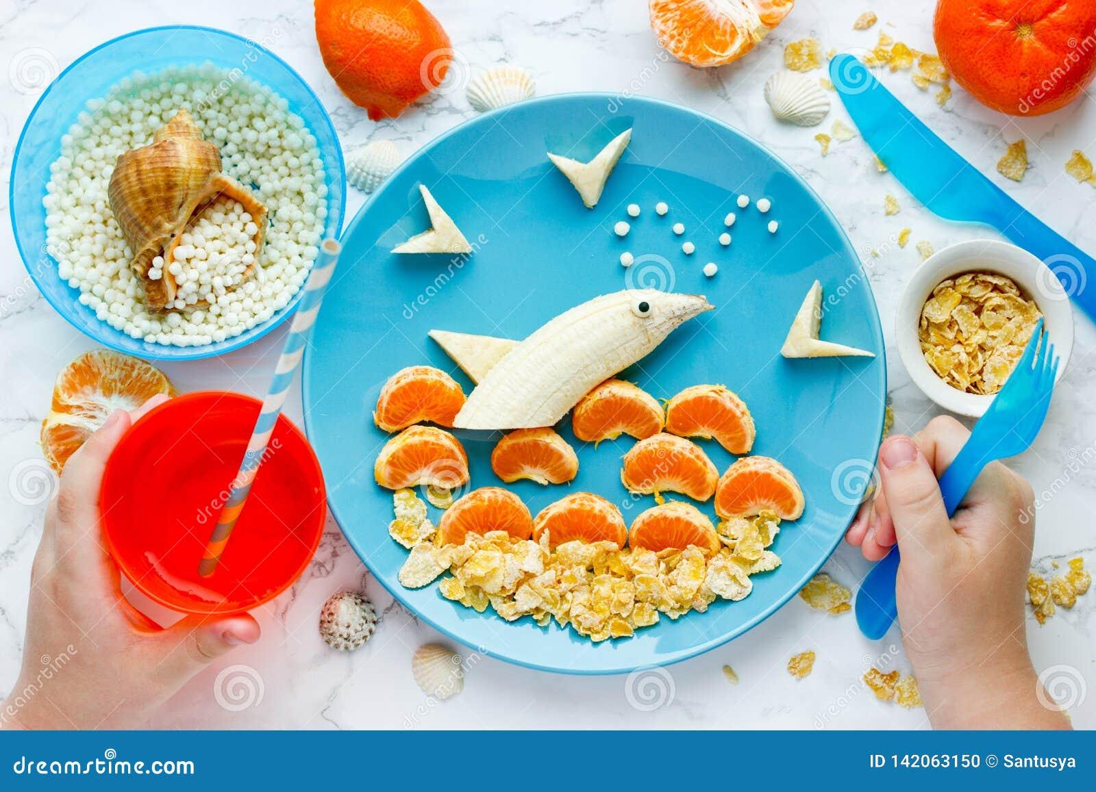 Diversión y comida sana para el delfín de la fruta de los niños