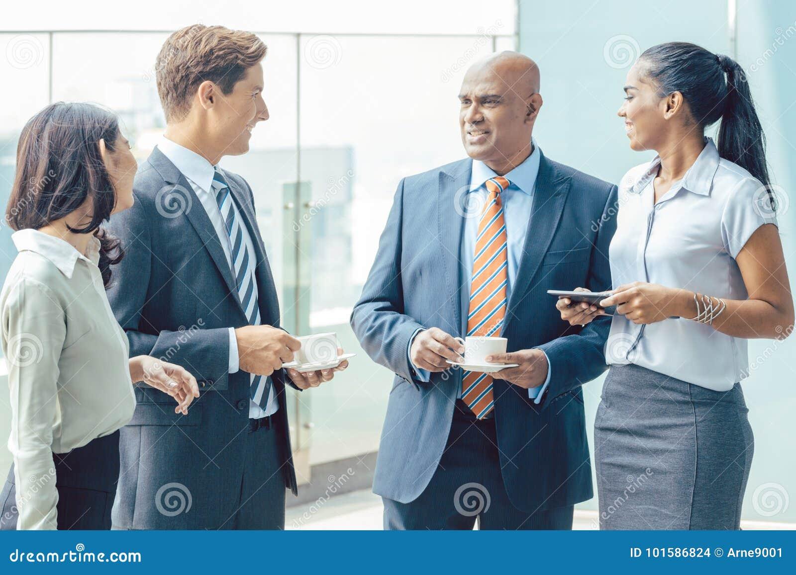 Diversiteits Aziatisch commercieel team met koffie voor bureau