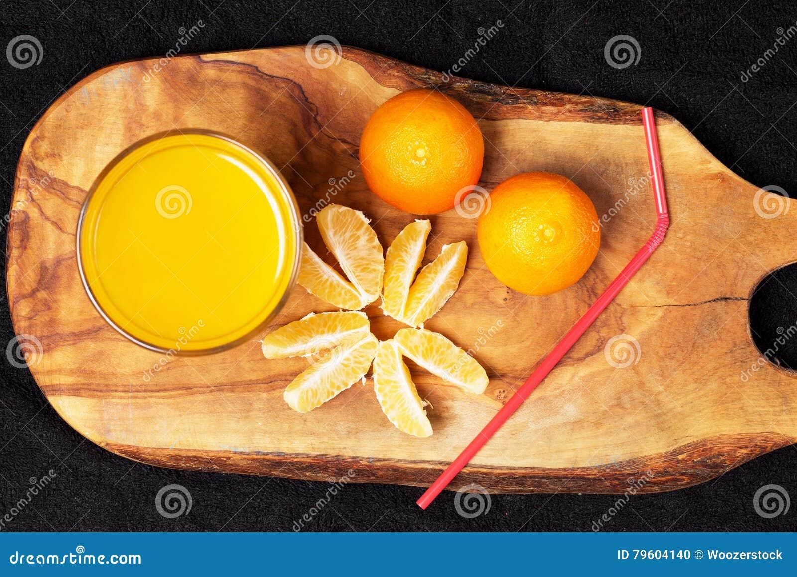 Diverso citrino maduro e um vidro do suco em uma tabela de madeira em um quadro-negro - os mandarino