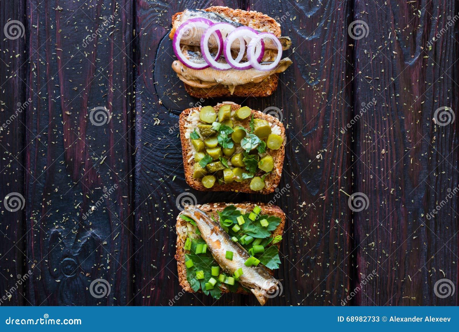 Diversos bocadillos con las verduras, el verdor y los pescados