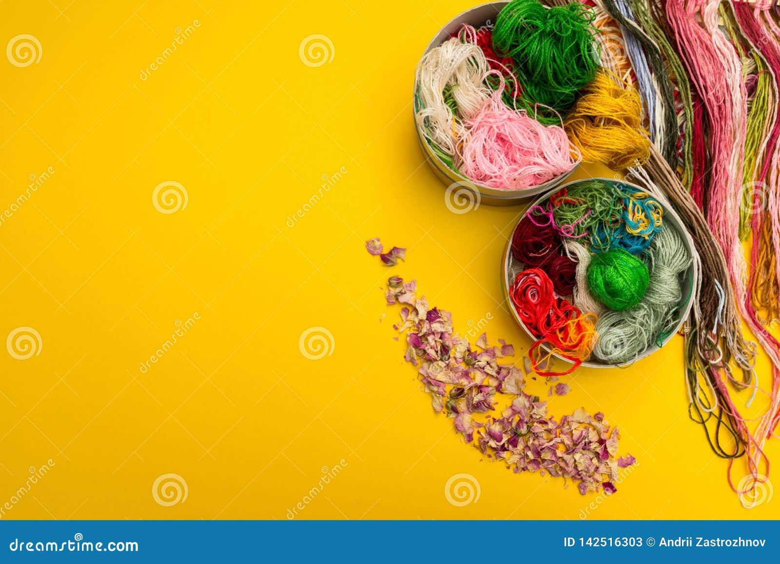 Diversos colores del hilo y de pétalos en un fondo amarillo