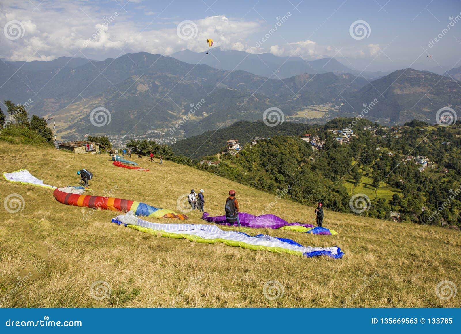 Diversos paragliders na inclinação estão preparando-se para decolar na perspectiva de uma montanha verde