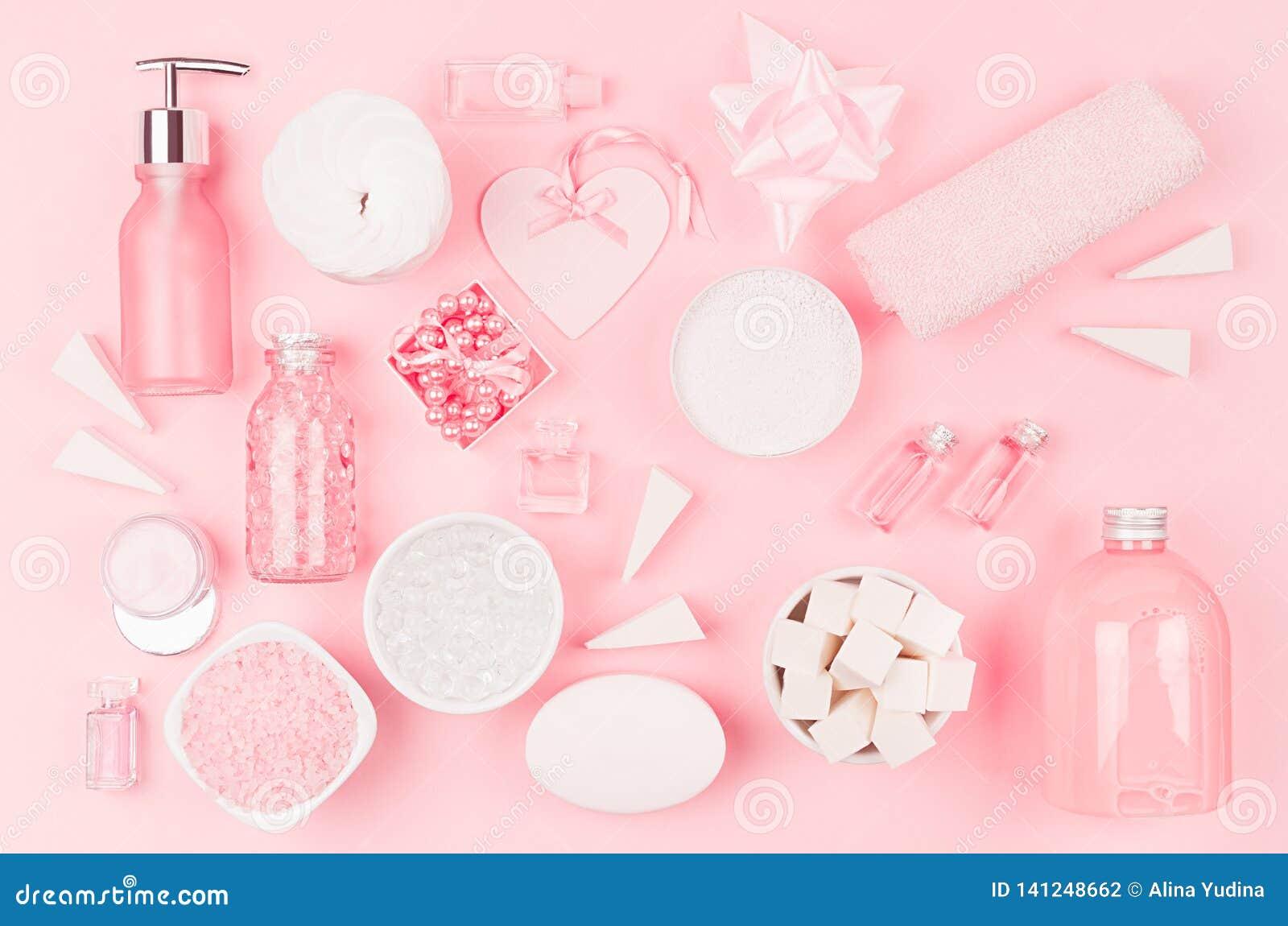 Diversos productos y accesorios cosméticos en rosa y color plata como modelo decorativo en el fondo rosa claro suave, visión supe