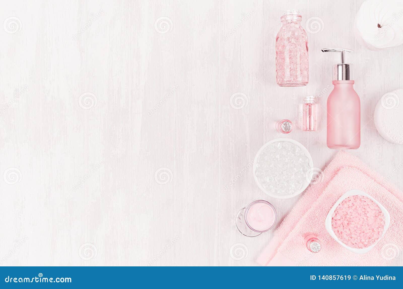 Diversos productos y accesorios cosméticos en rosado y color plata en el fondo de madera blanco ligero suave, espacio de la copia