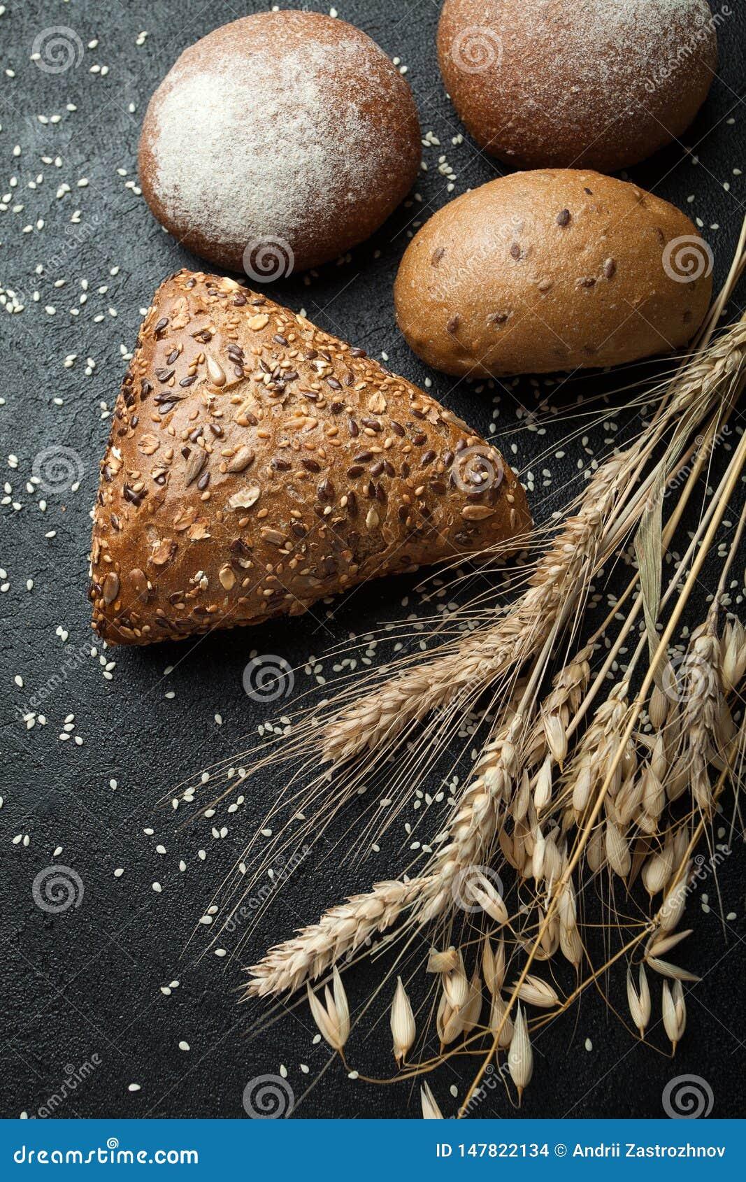 Diversos tipos hechos en casa de pan en un fondo oscuro rústico