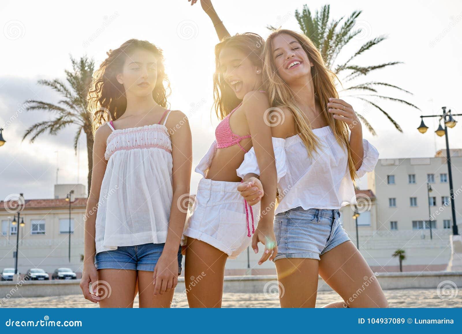 Divertimento adolescente das meninas dos melhores amigos em um por do sol da praia