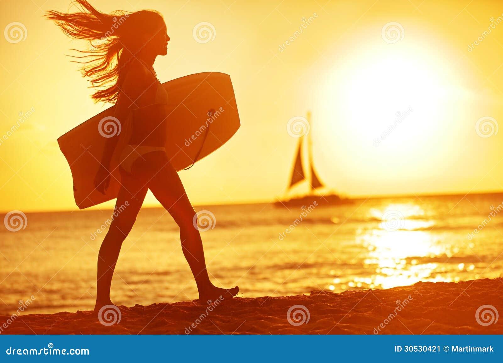 Divertimento da praia do surfista do corpo da mulher do verão no por do sol