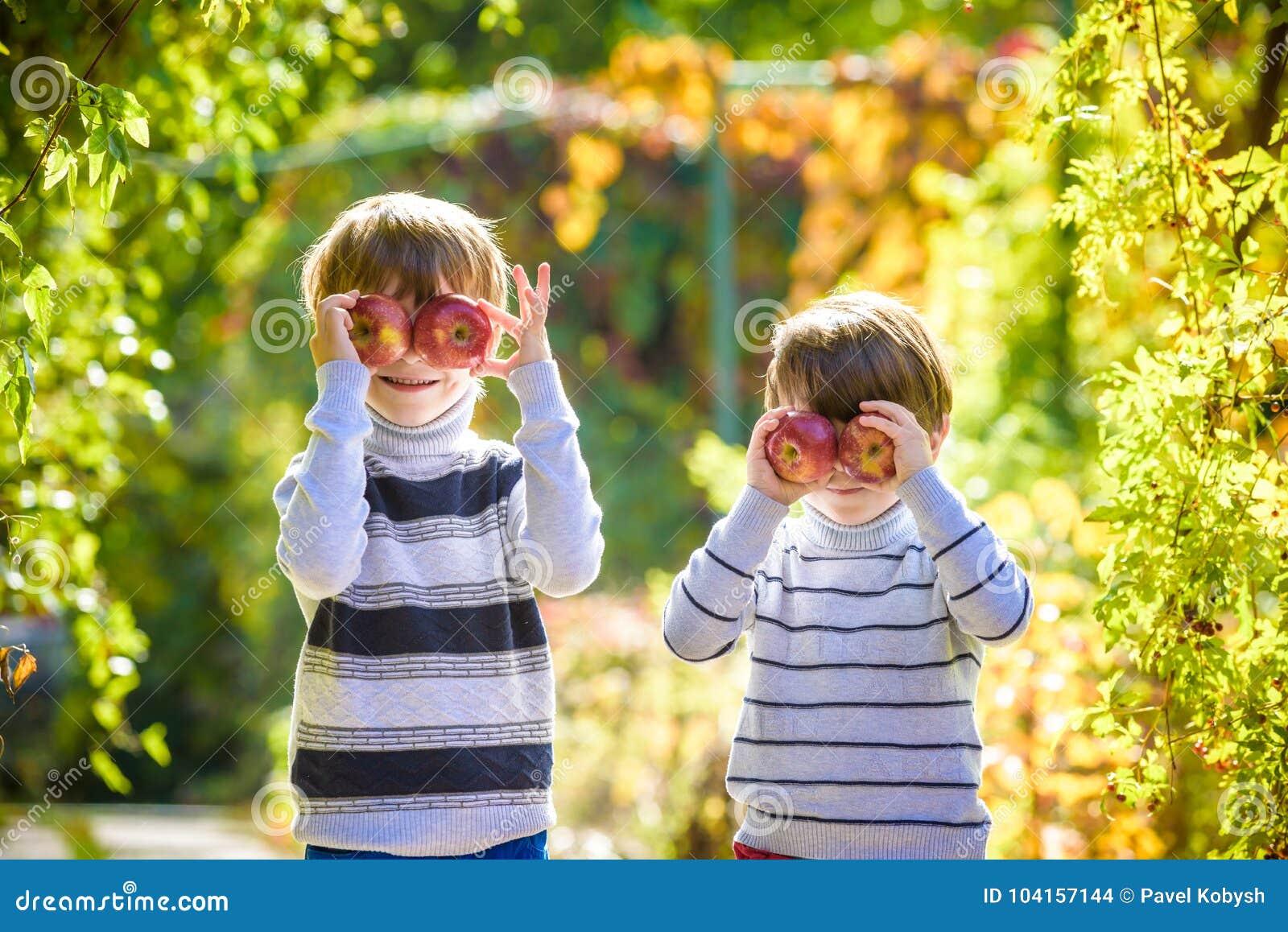 Divertimento della famiglia durante il tempo di raccolto su un azienda agricola Bambini che giocano nel giardino di autunno