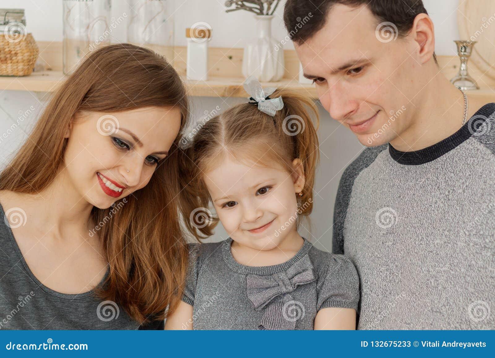 Divertimento e una bella famiglia di tre divertendosi nella cucina