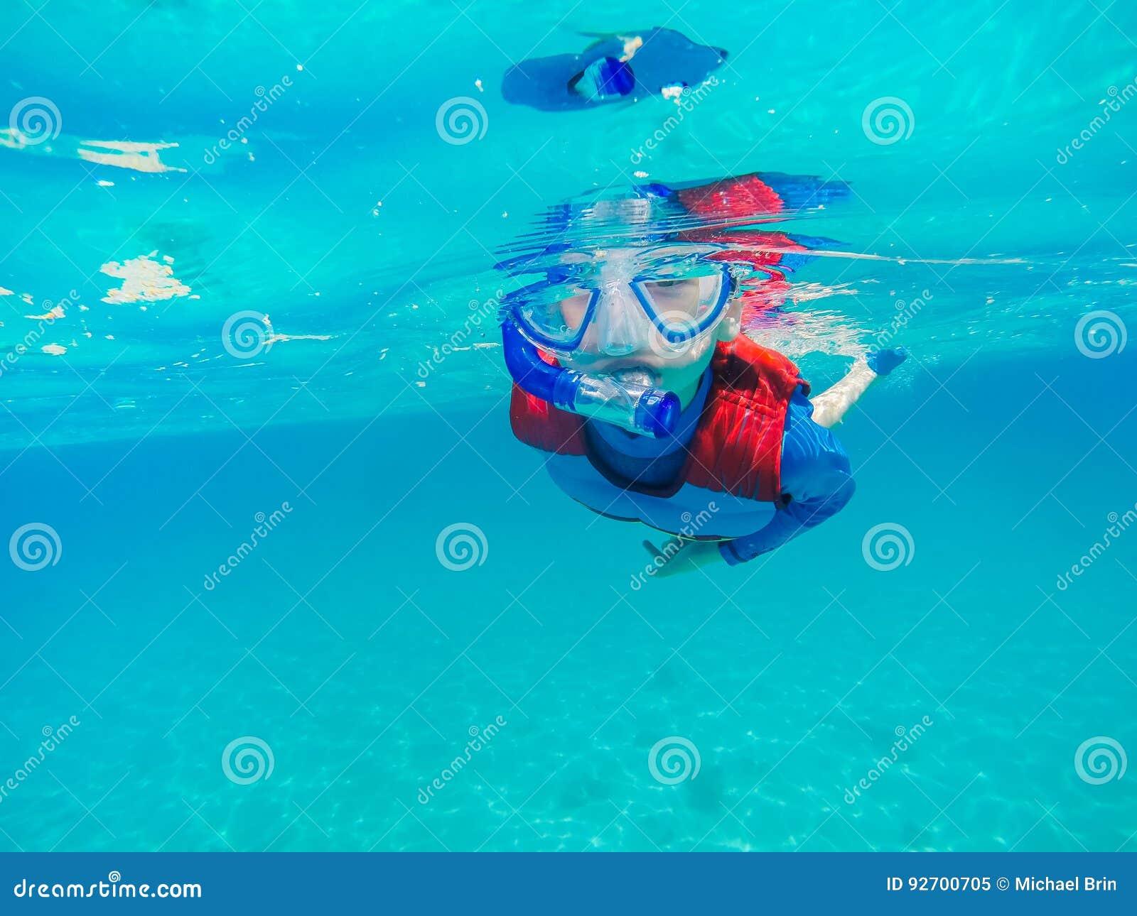 Divertimento novo subaquático do menino no mar com tubo de respiração Divertimento das férias de verão