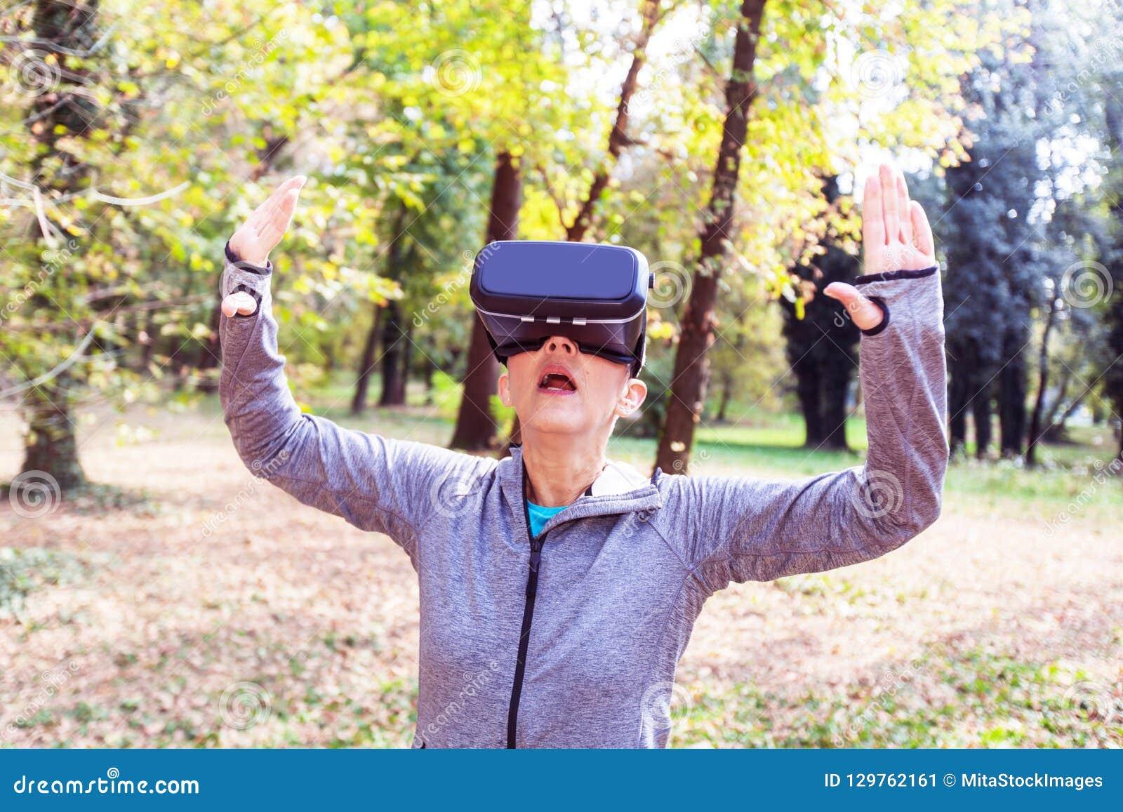 Divertimento superior da mulher com os auriculares da realidade virtual na floresta
