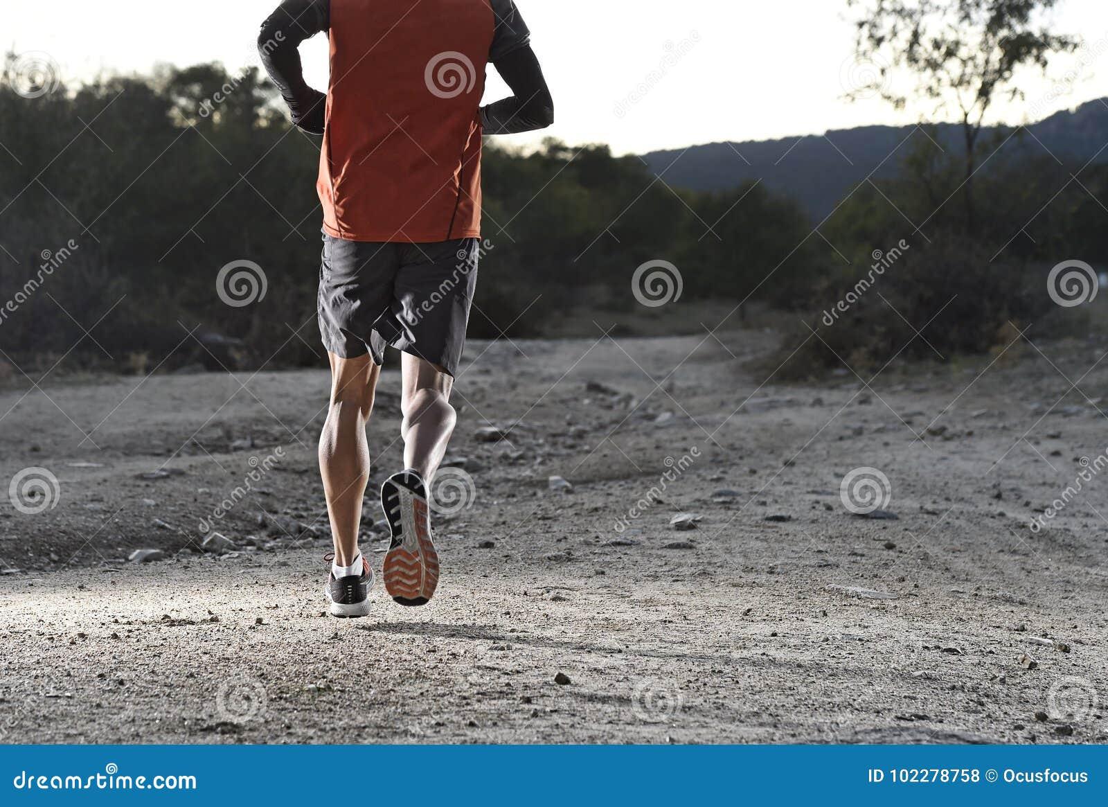 Diviértase al hombre con las piernas atléticas y musculares rasgadas que corren cuesta arriba del camino en entrenamiento del ent