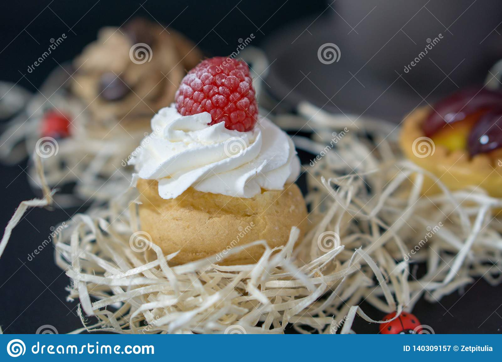 Divine cakes with raspberries and cream, the background is blurred with other cak