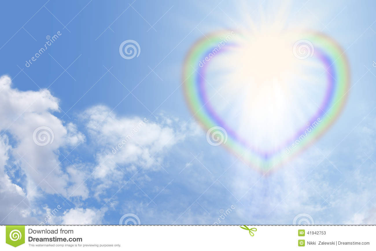 Heart shaped rainbow bursting with light on a blue sky background ...