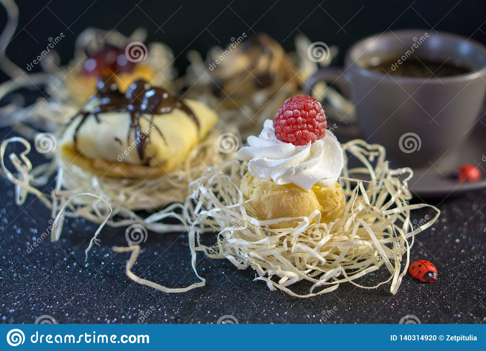 Divine pastries with raspberries and cream, with a bottom under the cake, blur the background with other pastries and a