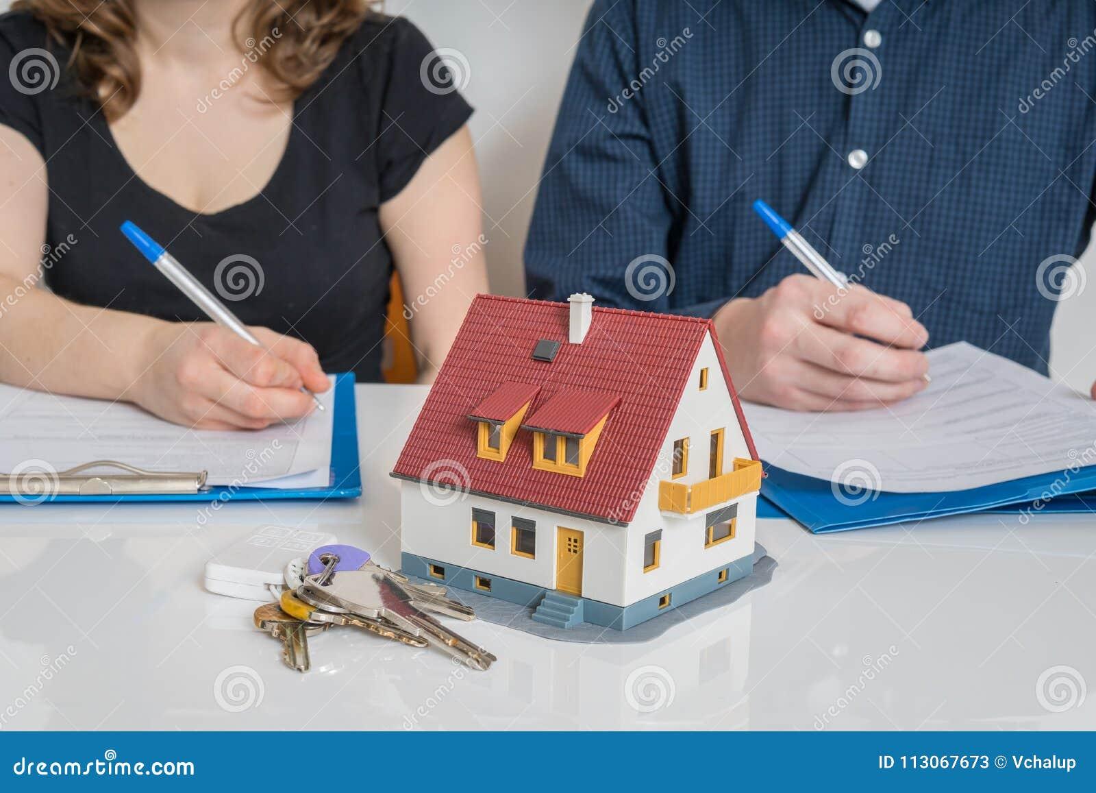 Divorzi e dividendo un concetto della proprietà L uomo e la donna stanno firmando l accordo di divorzio