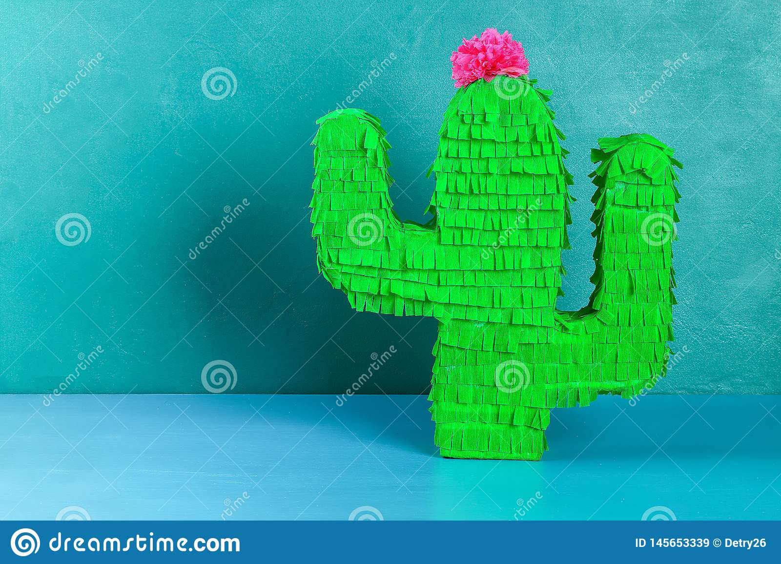 Diy cinco de mayo Mexican Pinata Cactus made cardboard, crepe paper your own hands blue background