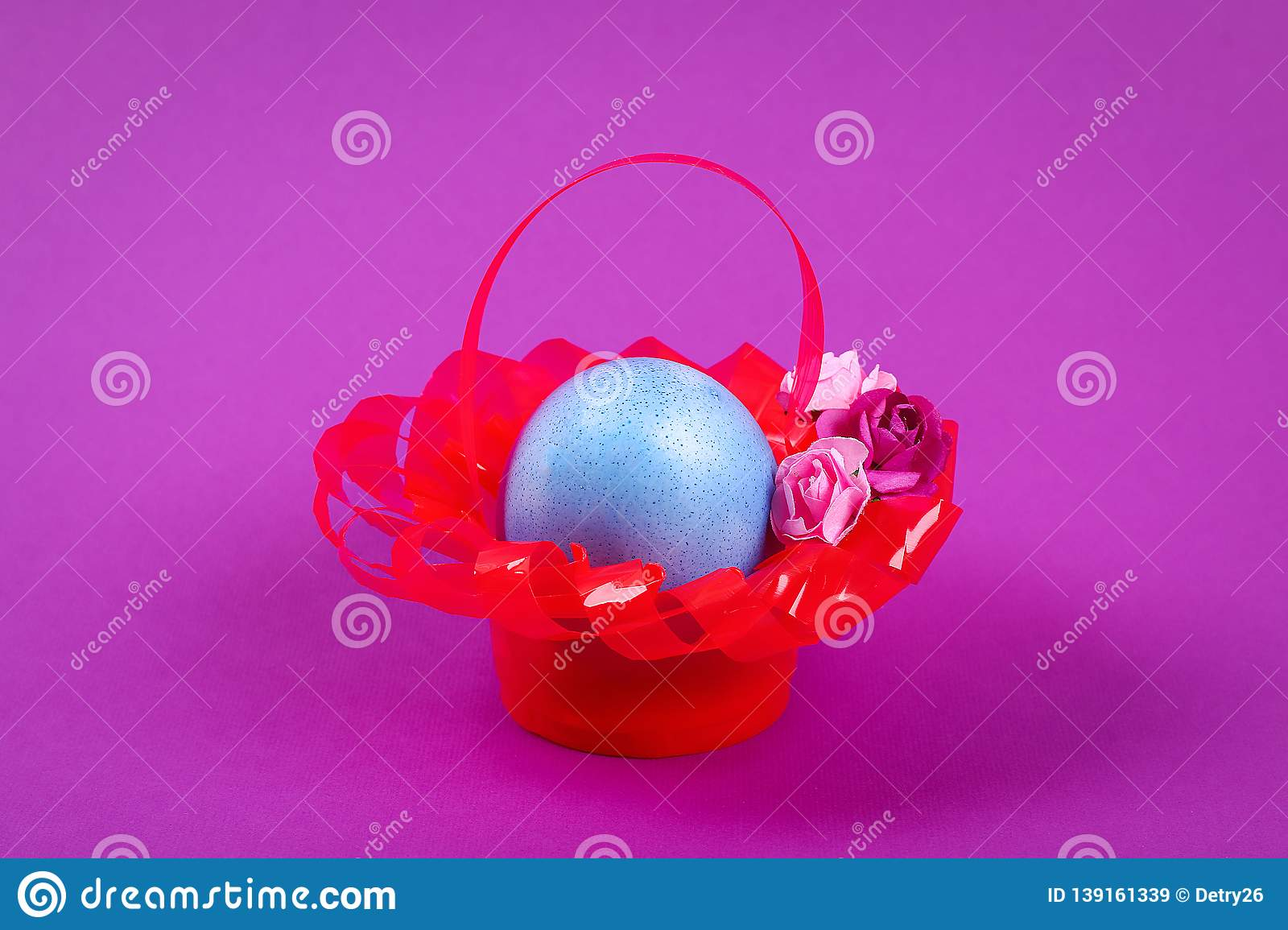 Diy Easter egg basket made of red plastic cup decorated with artificial flowers purple background