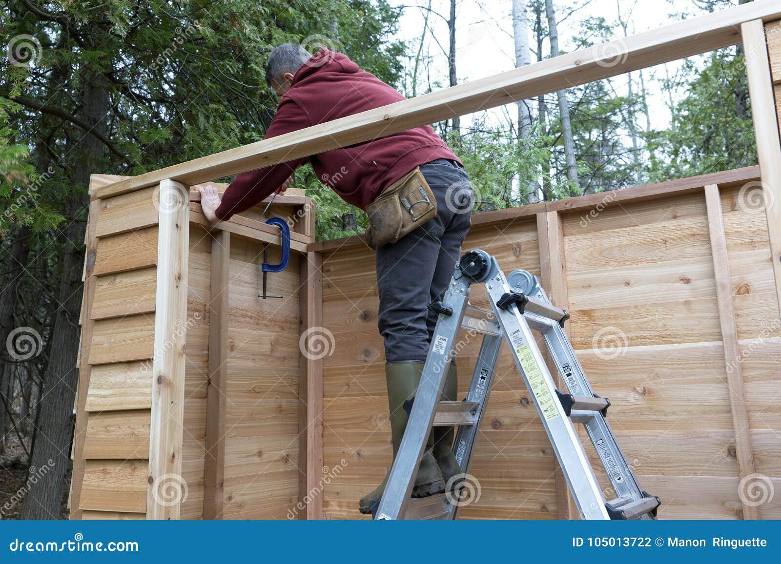 Handyman Building A Cedar Storage Shed Stock Photo - Image