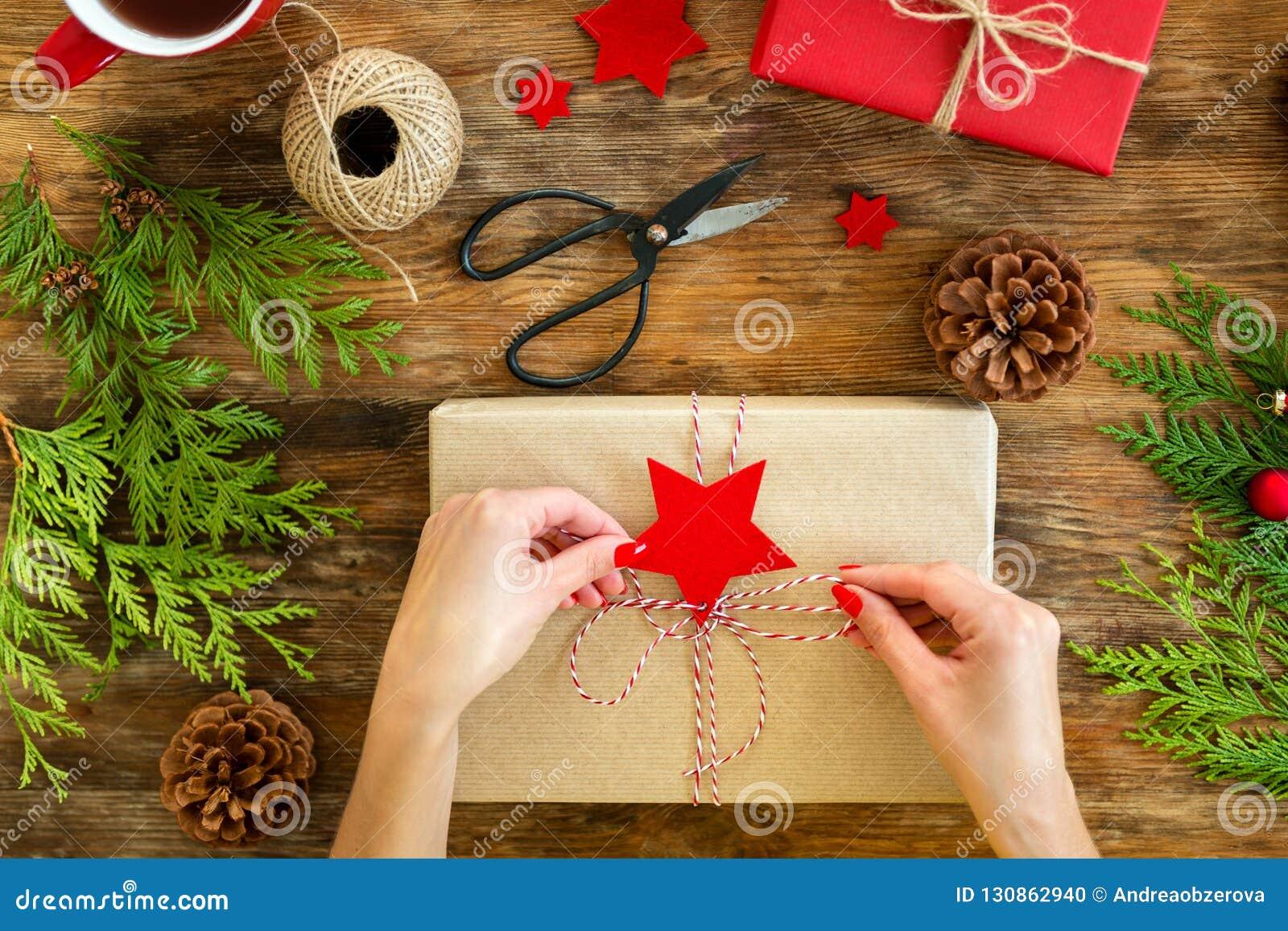 DIY-Gift het Verpakken Vrouw die mooie rode Kerstmisgiften op rustieke houten lijst verpakken Het luchtmeningskerstmis verpakken