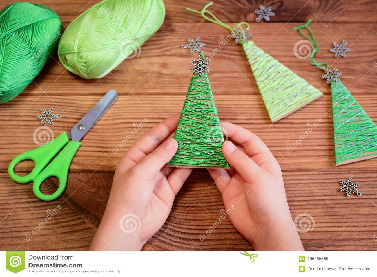 download kid is holding a christmas tree decoration in his hands kid is showing a - Childrens Christmas Tree Decorations