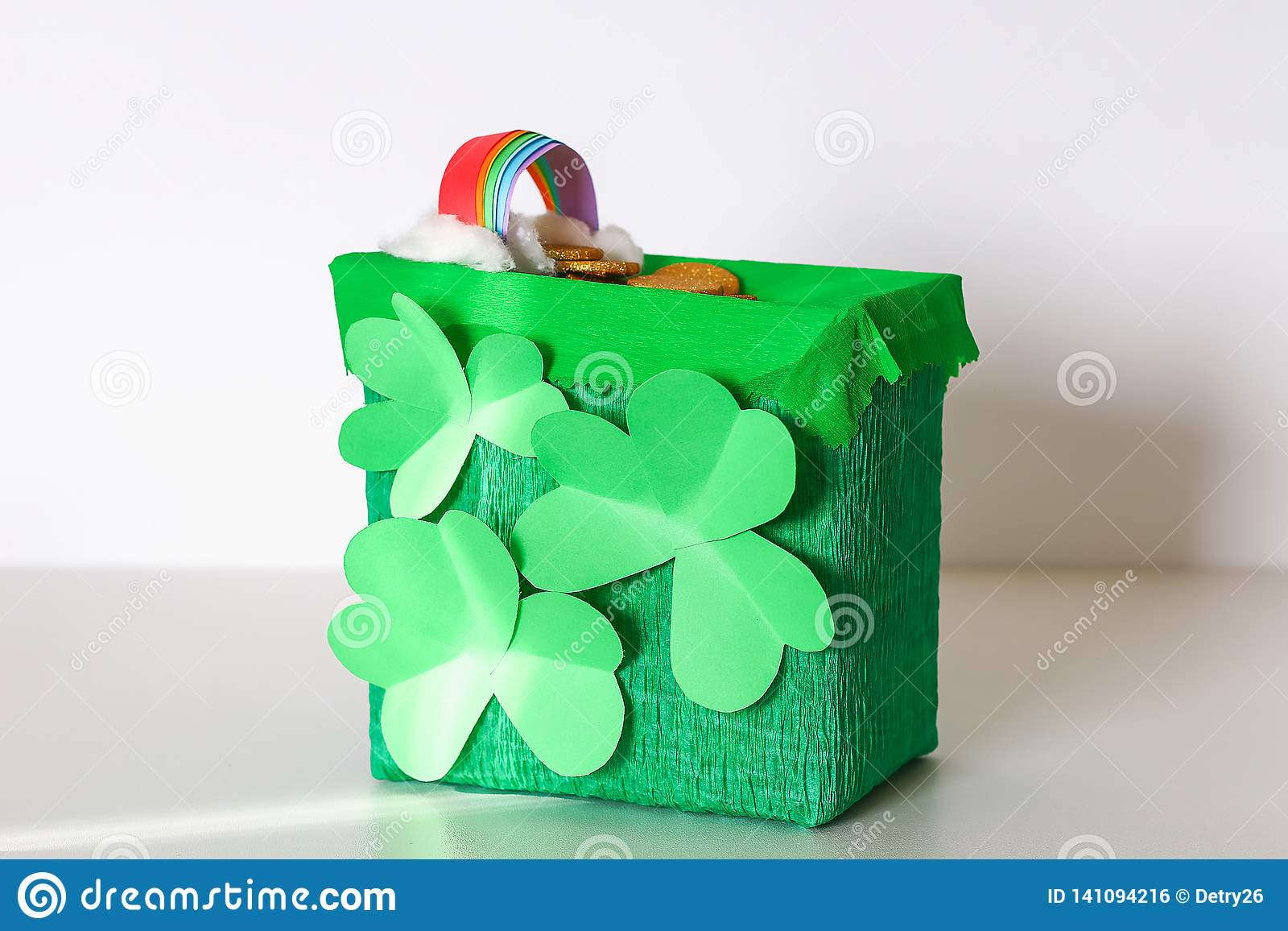 DIY leprechaun trap with gold coins, rainbow and green ladder St Patricks Day background