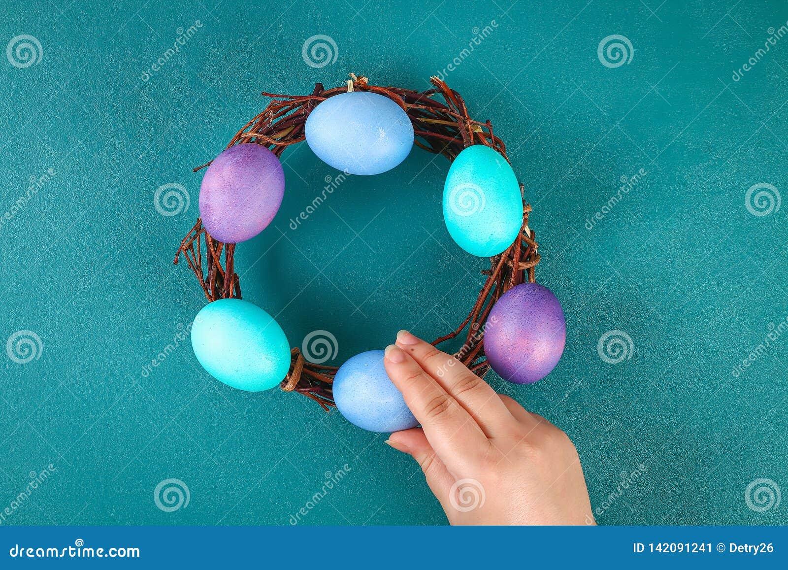 Diy Wielkanocny wianek gałązki, malujący jajka i sztuczni kwiaty na zielonym tle,