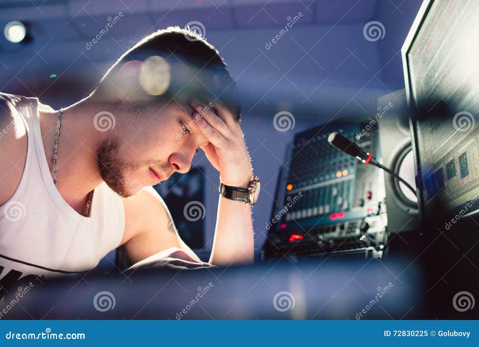 DJ cansado que se sienta en el primer del estudio