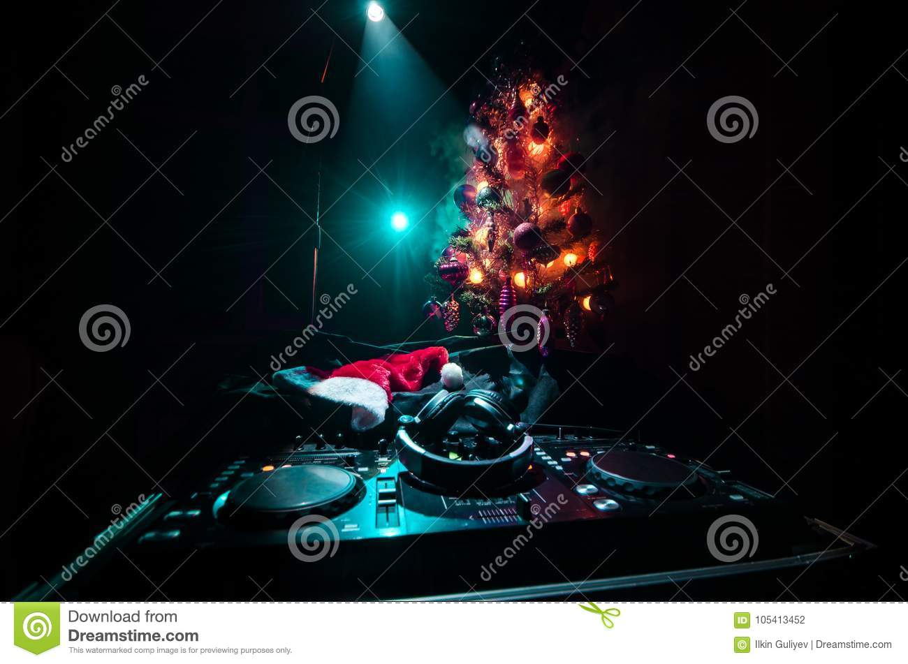 Dj mixer with headphones on dark nightclub background with Christmas tree New Year Eve. Close up view of New Year elements or symb