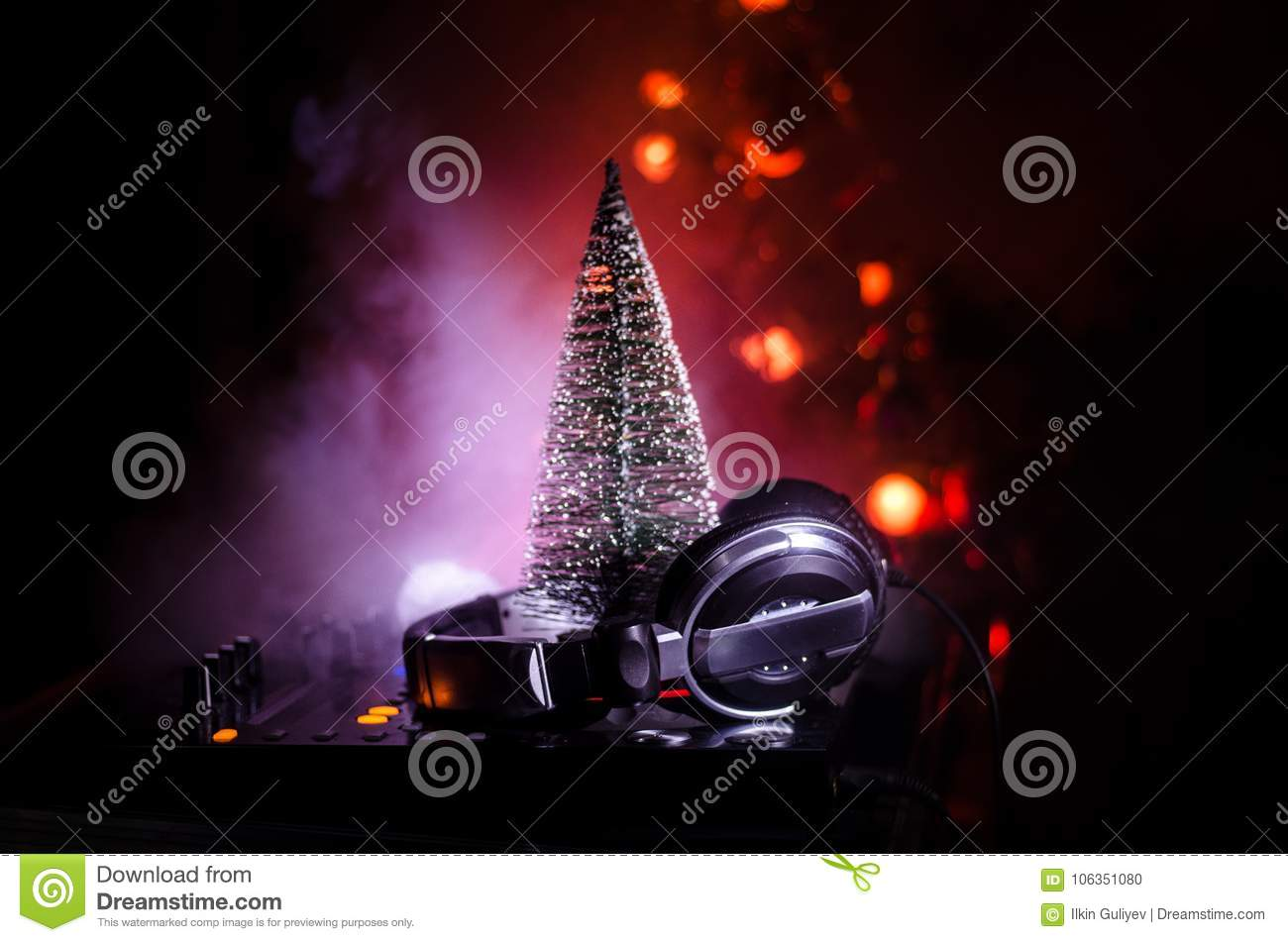 dj mixer with headphones on dark nightclub background with christmas tree new year eve close