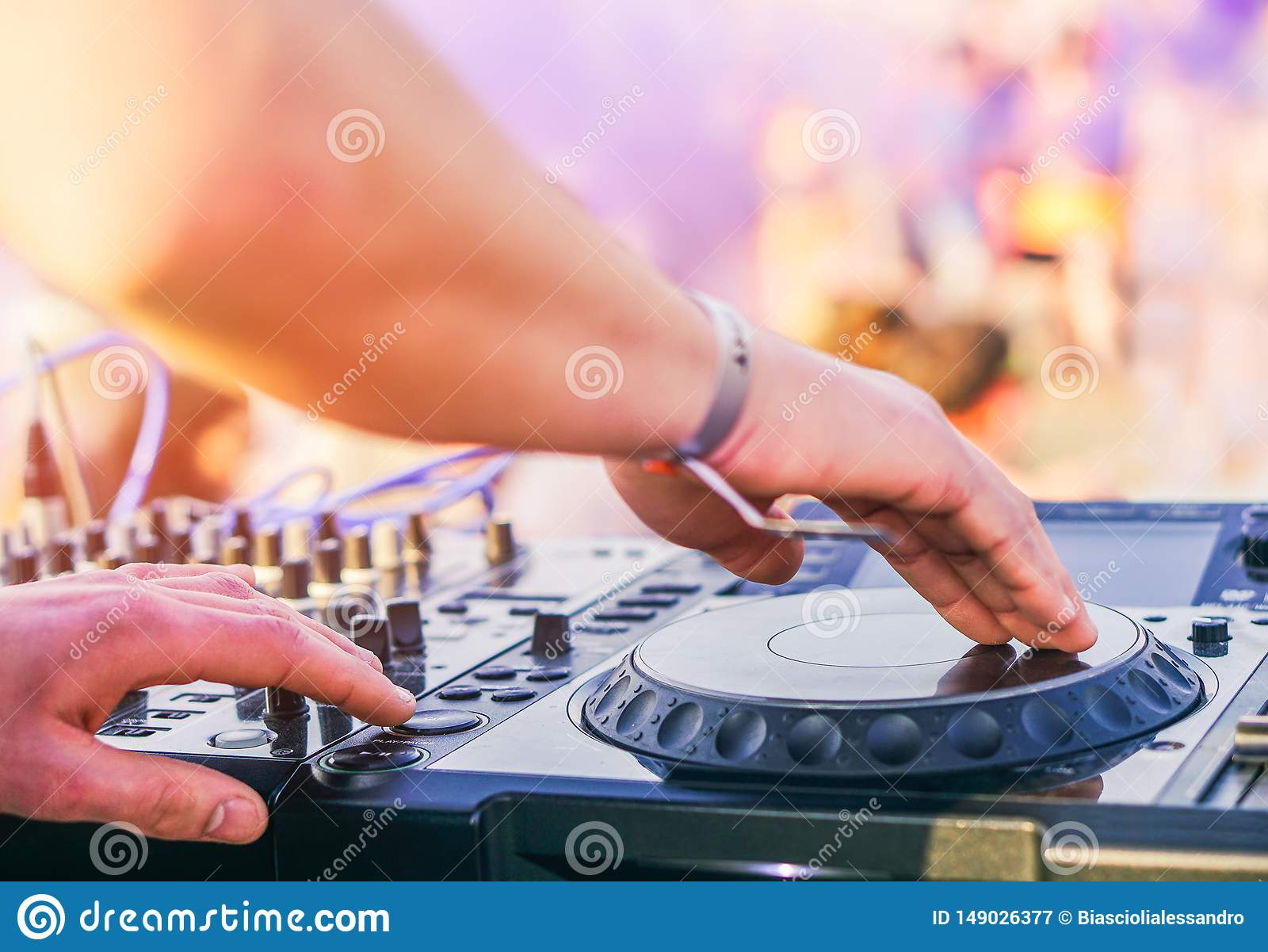 Dj mixing at beach party festival with people dancing in the background - Deejay playing music mixer audio outdoor