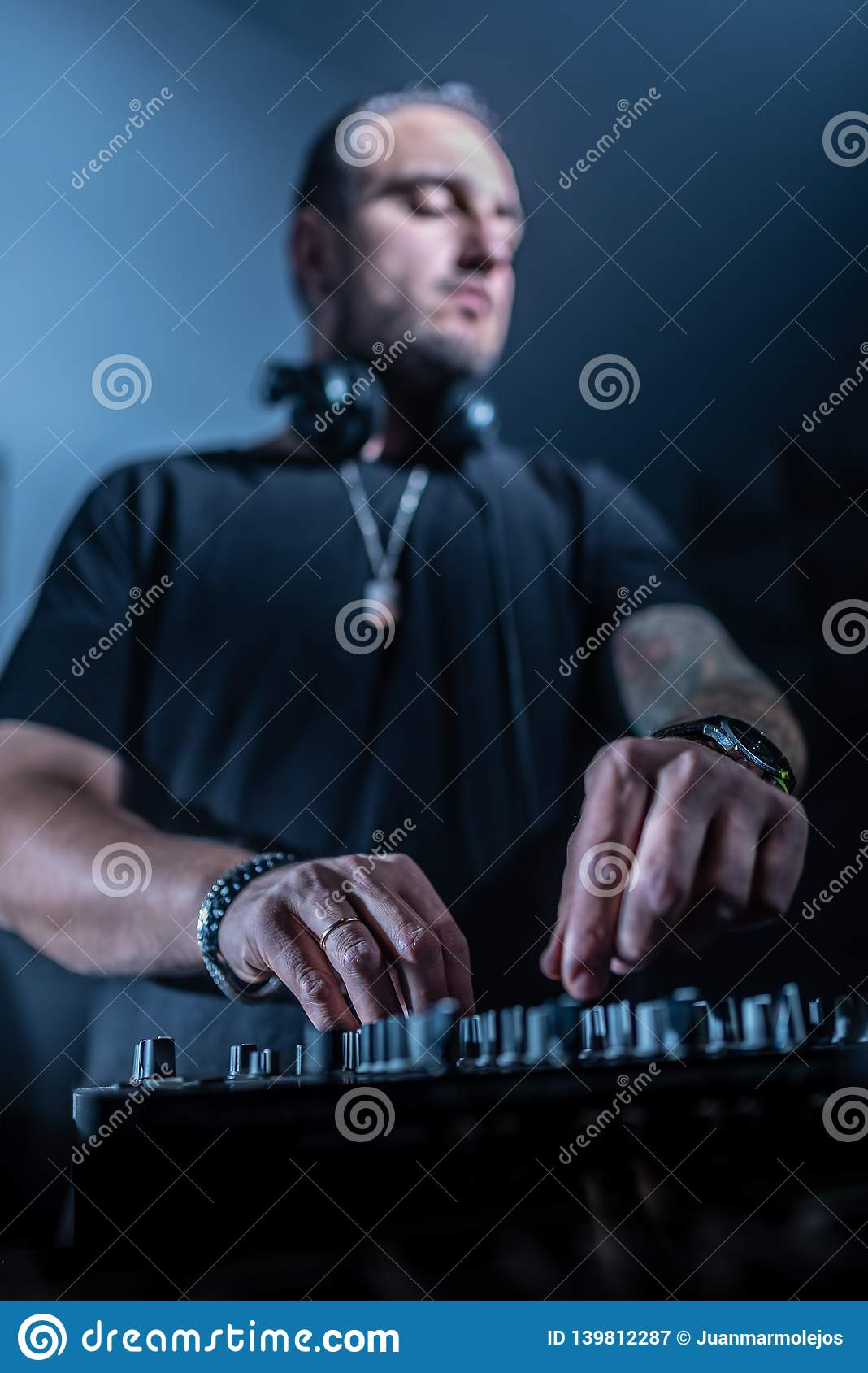 DJ playing house and techno music in a night club. Mixing and controlling the music