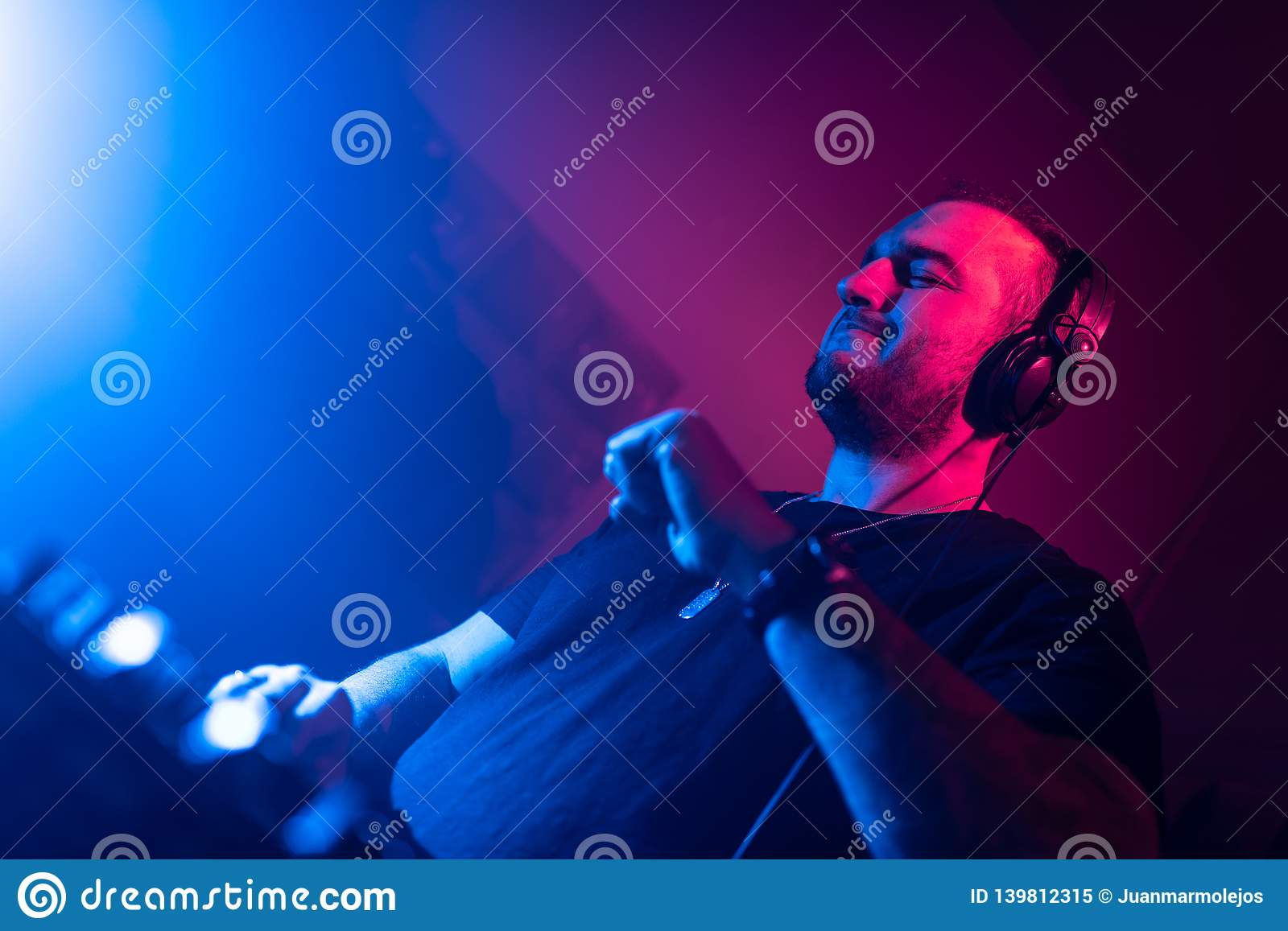 DJ Playing House And Techno Music In A Night Club  Mixing
