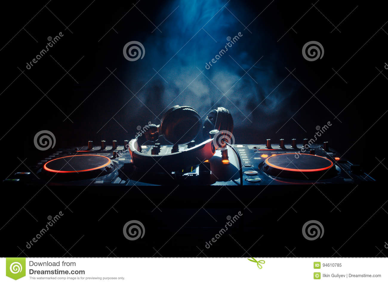 DJ Spinning, Mixing, and Scratching in a Night Club, Hands of dj tweak various track controls on dj s deck, strobe lights and fog