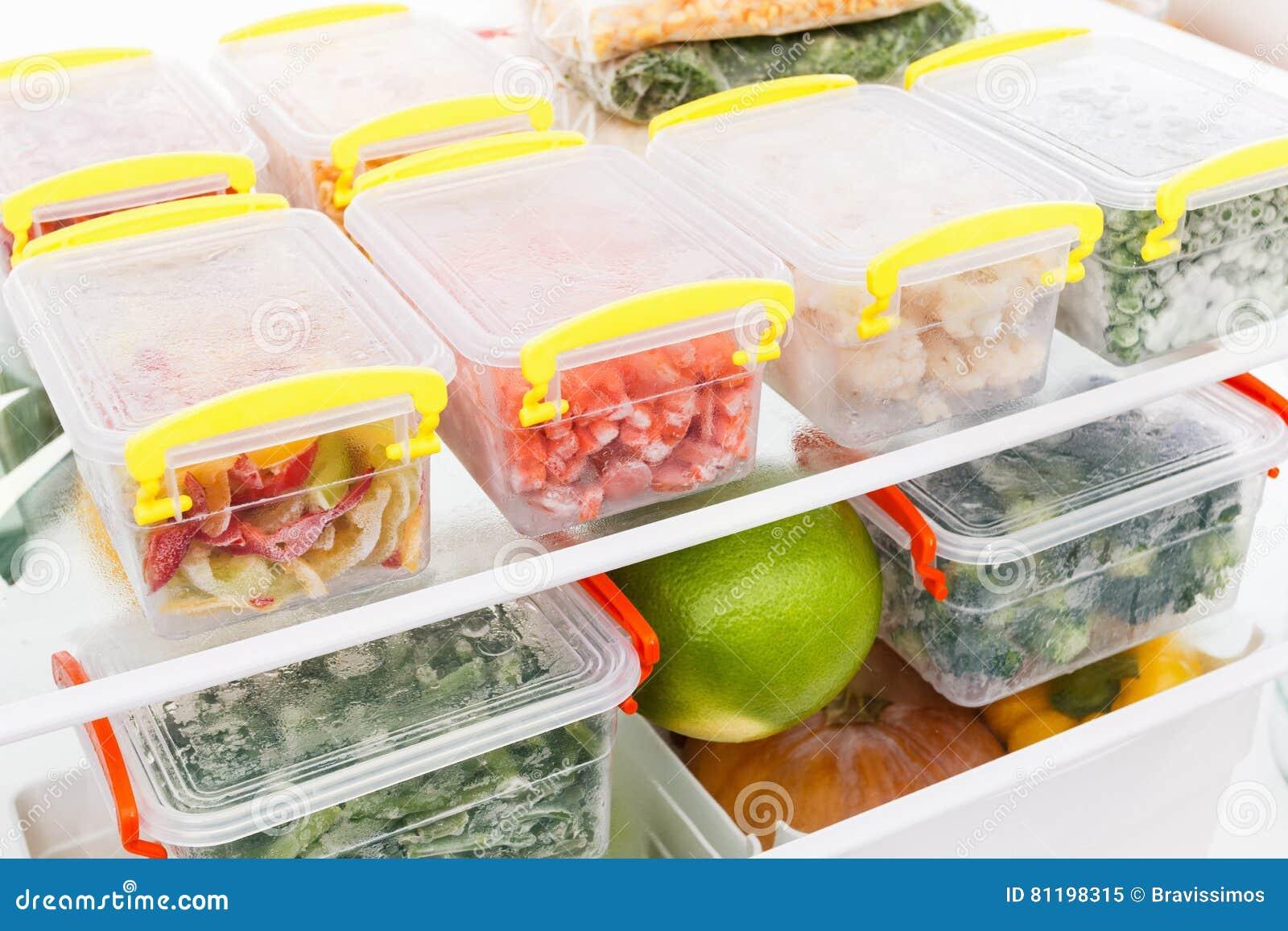 Djupfryst mat i kylskåpet Grönsaker på fryshyllorna