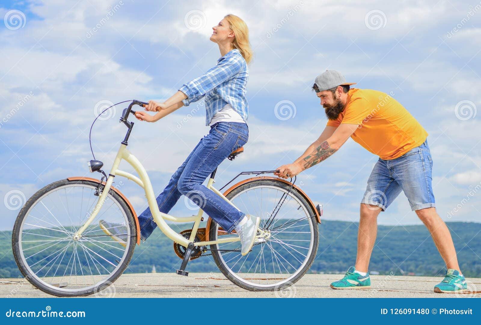 Dlaczego uczyć się jechać rower jako dorosły Dziewczyny kolarstwo podczas gdy chłopak wspiera ona Uczy dorosłego przejażdżka rowe