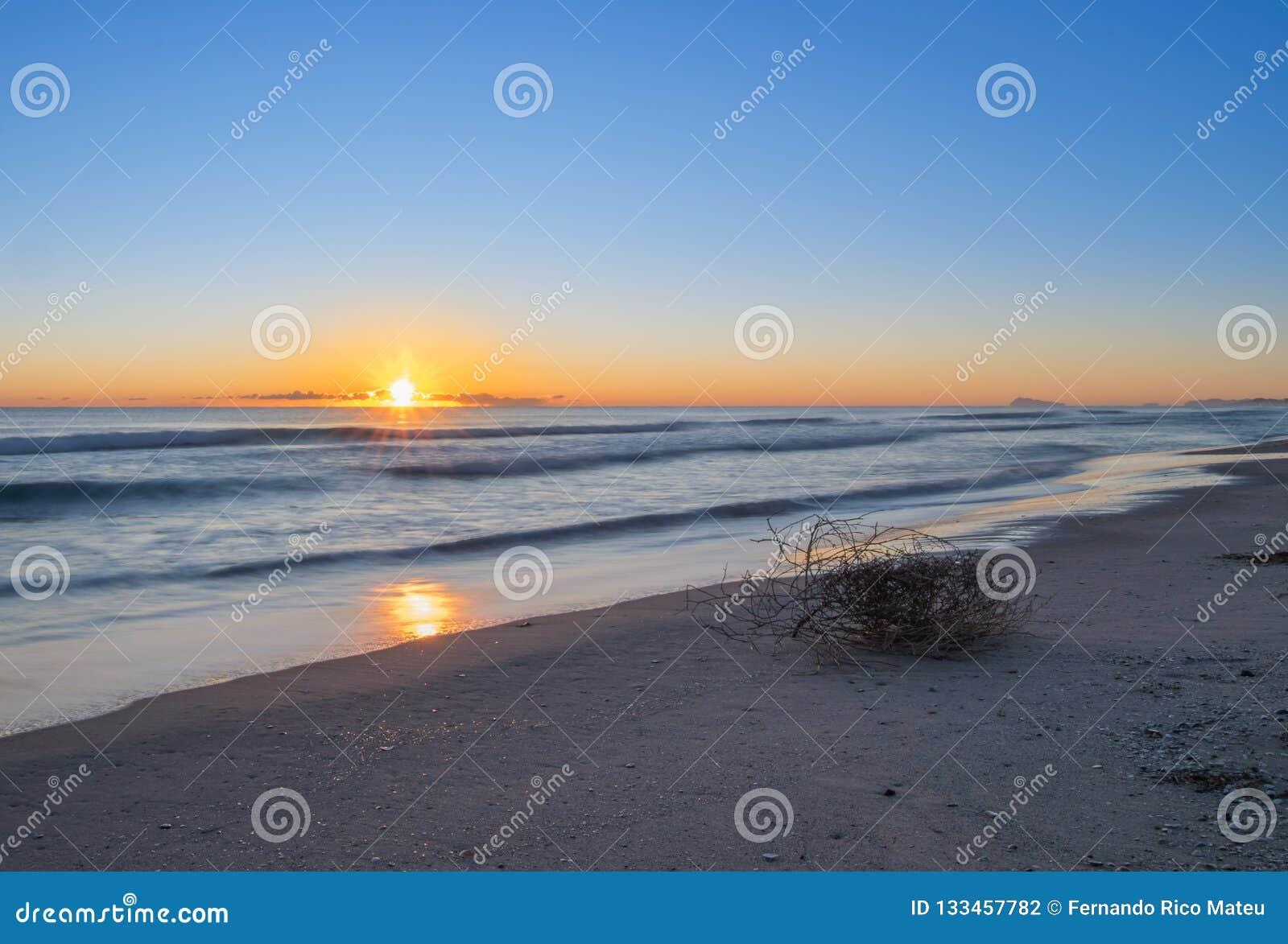 Dnieje na plaży, piękny gwiaździsty słońce nad horyzontem Długi ujawnienie na Walencja plaży