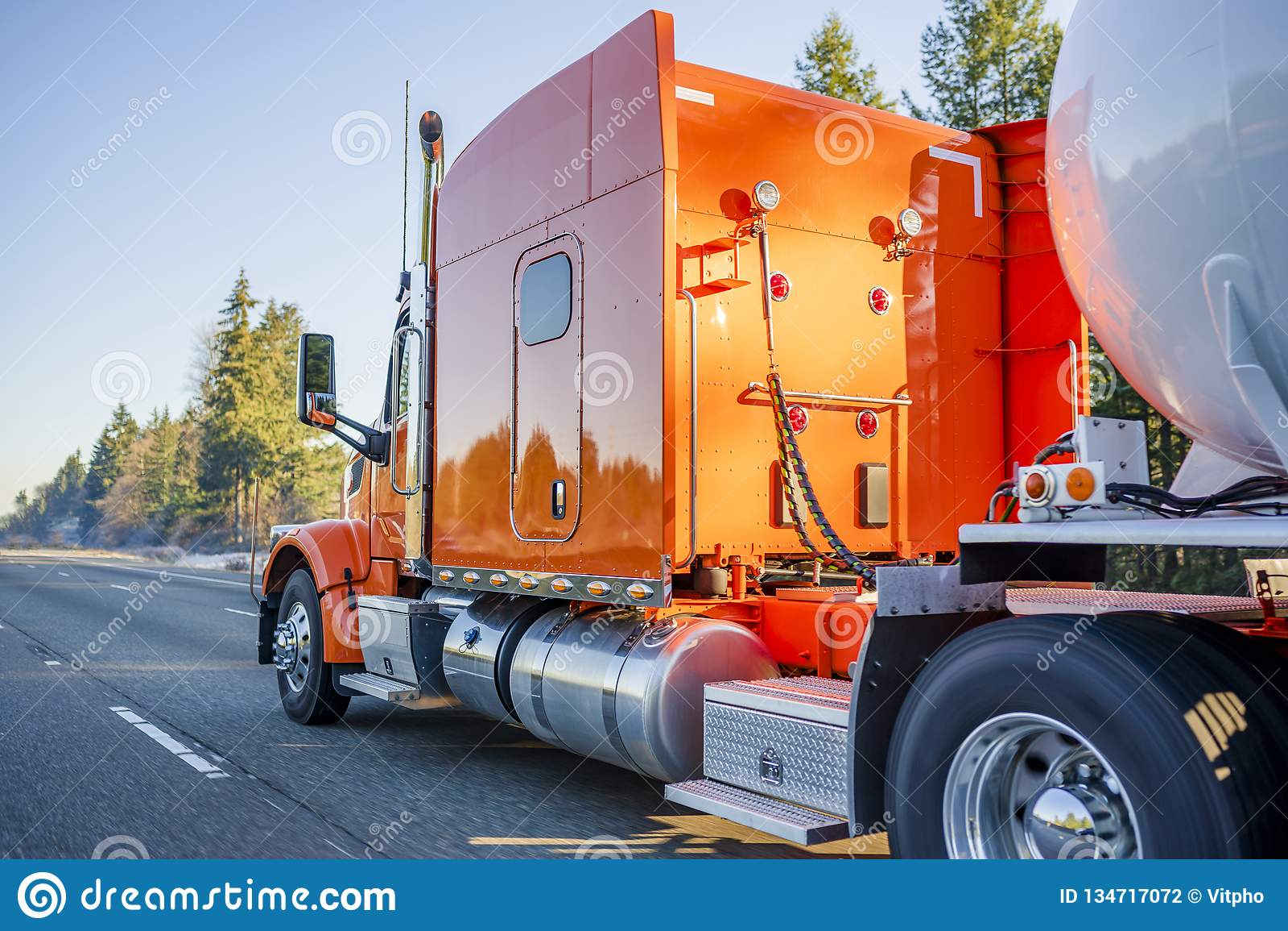 Do equipamento caminhão grande alaranjado brilhante semi que transporta o reboque do tanque semi para o transporte do corredor qu