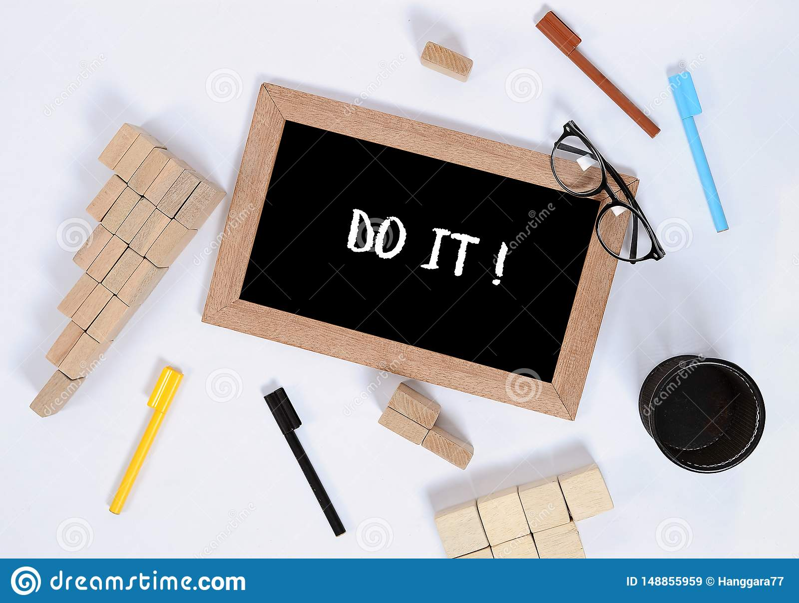 Do it text on blackboard with office accessories. Business motivation, inspiration concepts, pen and pencil case, wood block