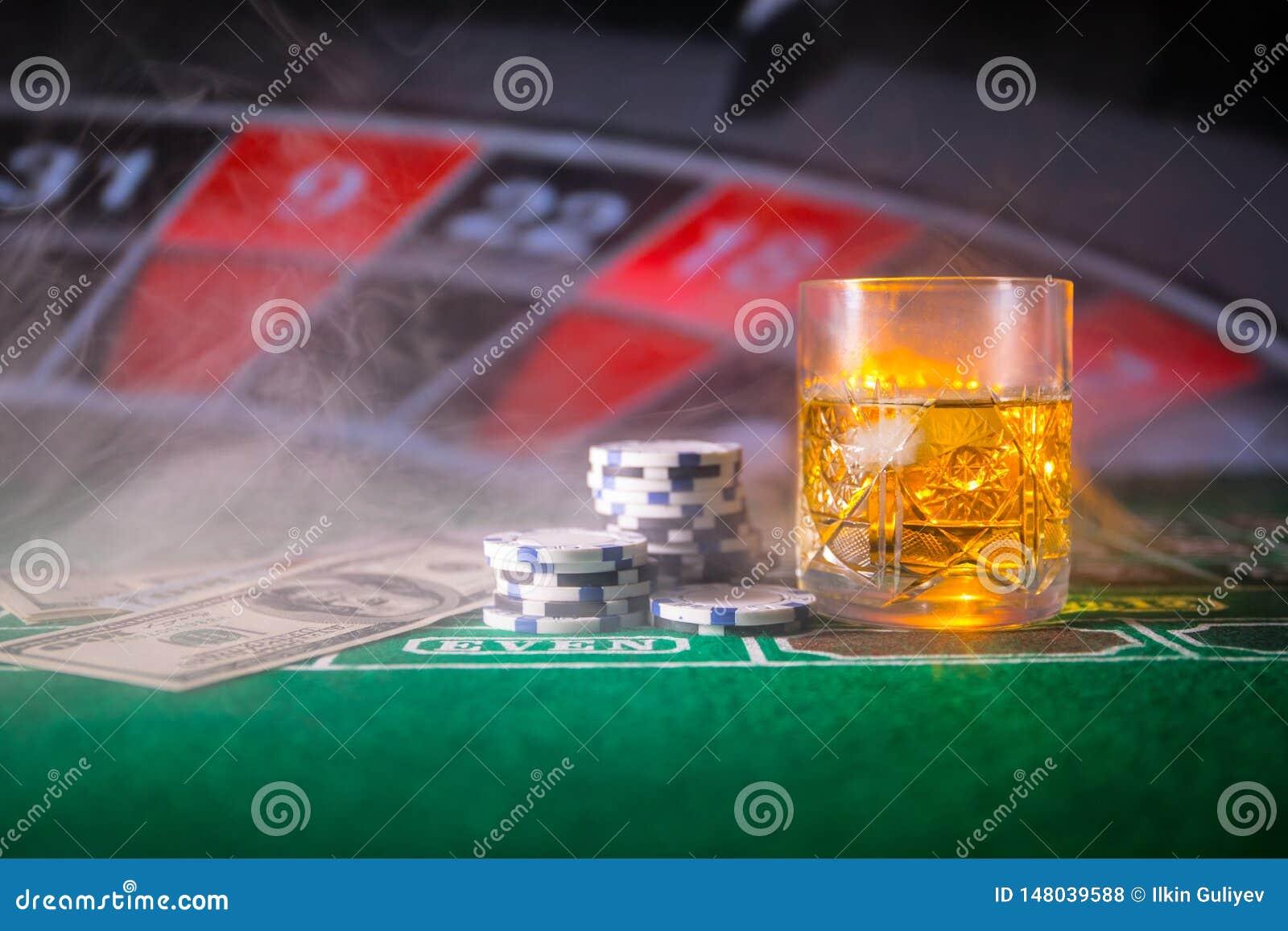 Dobbleri-, f?rm?genhet-, lek- och underh?llningbegrepp - som ?r n?ra upp av kasinochiper och whiskyexponeringsglas p? tabellen
