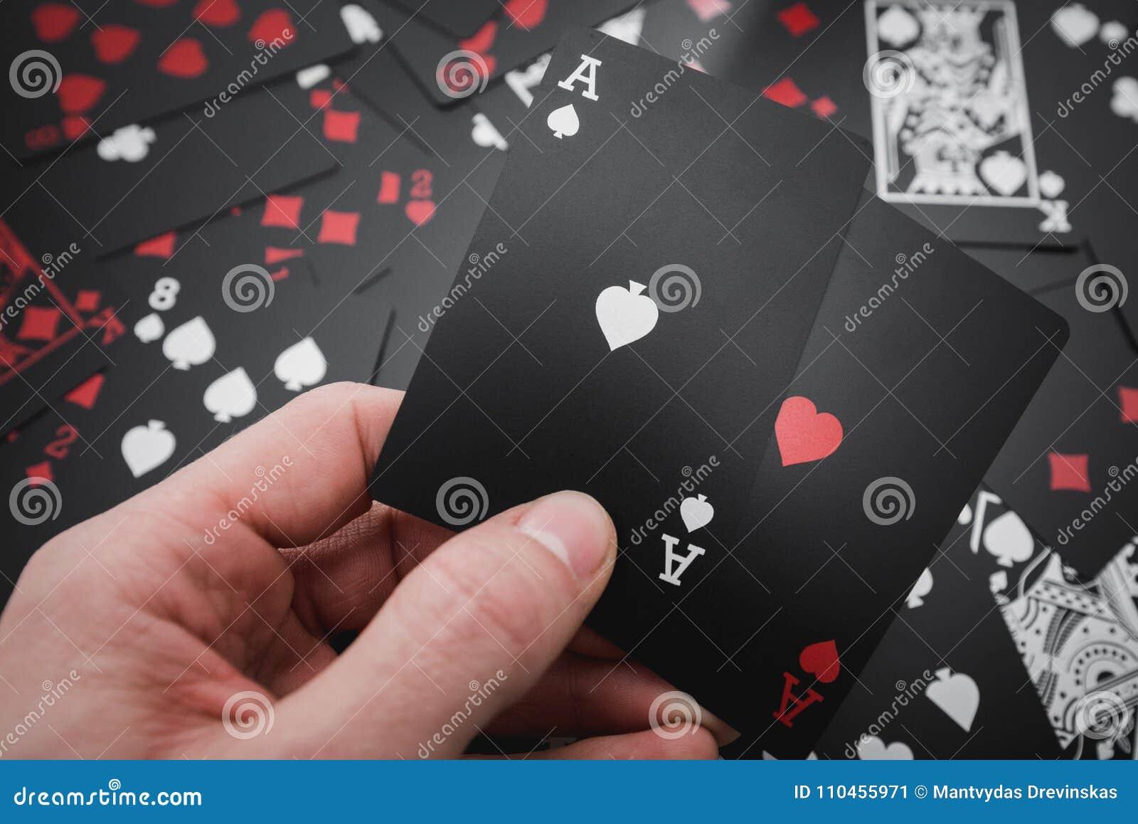 Dobbleri Två överdängare i hand i svart färgade spela kortbakgrund