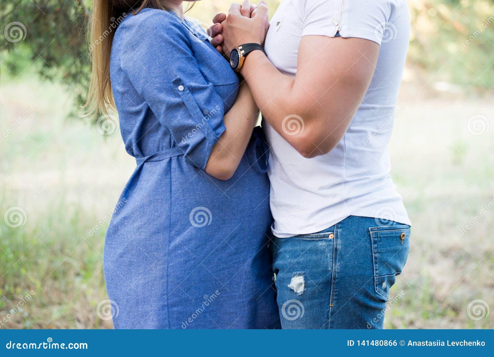Dobiera się w miłości ciężarny cuddling, czekać na dziecka odprowadzenie w parku w ciepłym słonecznym dniu Brzemienność niebieski